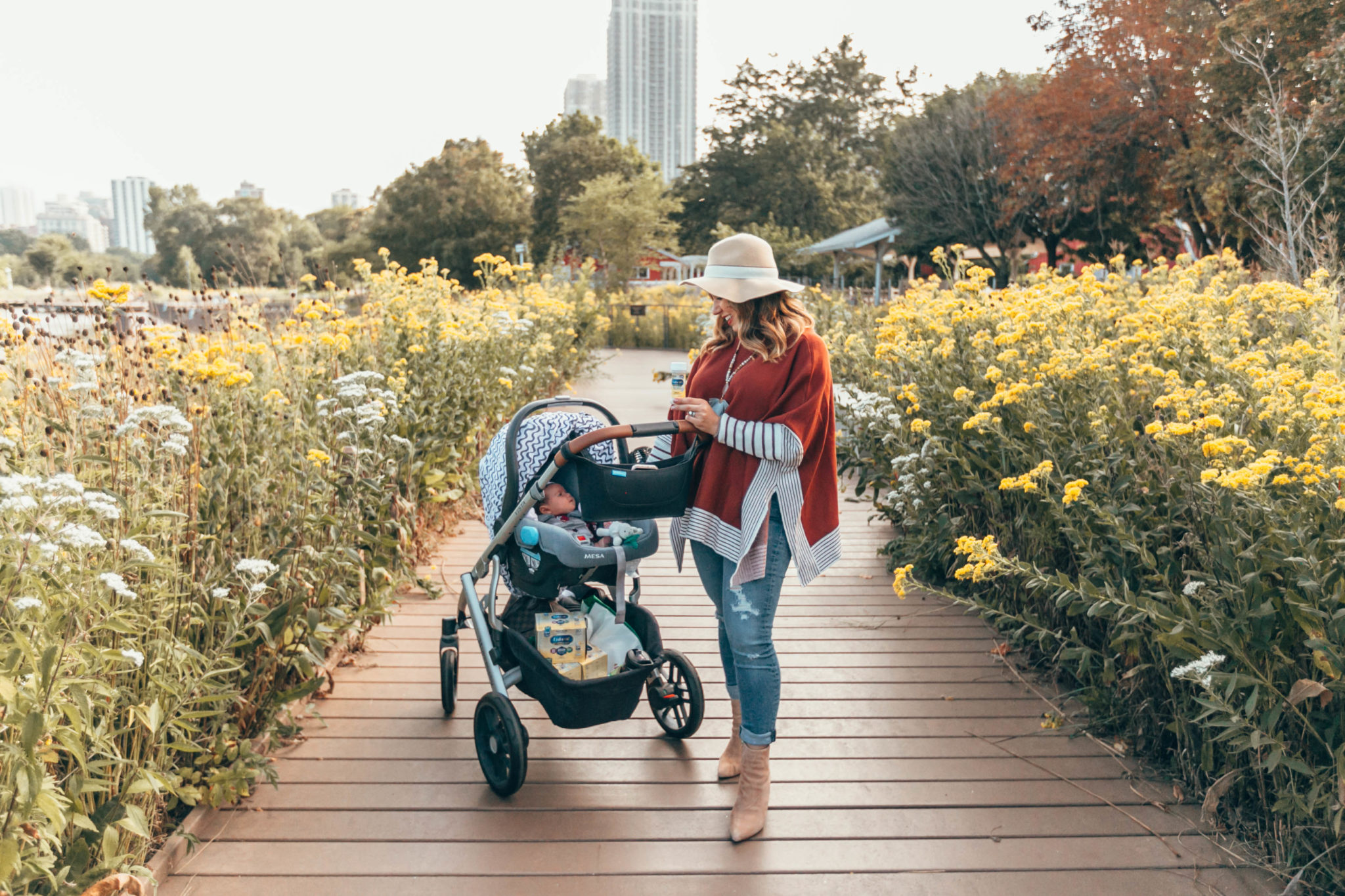 Enfamil NeuroPro Infant Formula Is My Baby Formula Choice by popular Chicago mom blog, Glass of Glam: image of a mom pushing her baby in a stroller outside and holding a bottle of Enfamil NeuroPro Infant Formula.