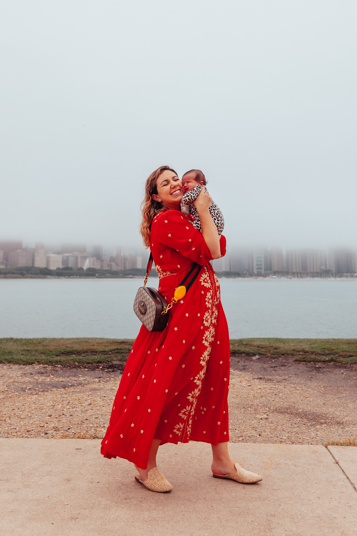 My New Mom Morning Routine by popular Chicago mom blog, Glass of Glam: image of a mom walking outside with her newborn baby and wearing an Anthropologie Embroidered Fable Midi Dress, STEVE MADDEN MATTIS MULE, Gucci GG Supreme messenger bag, and Little Me Leopard Footie.
