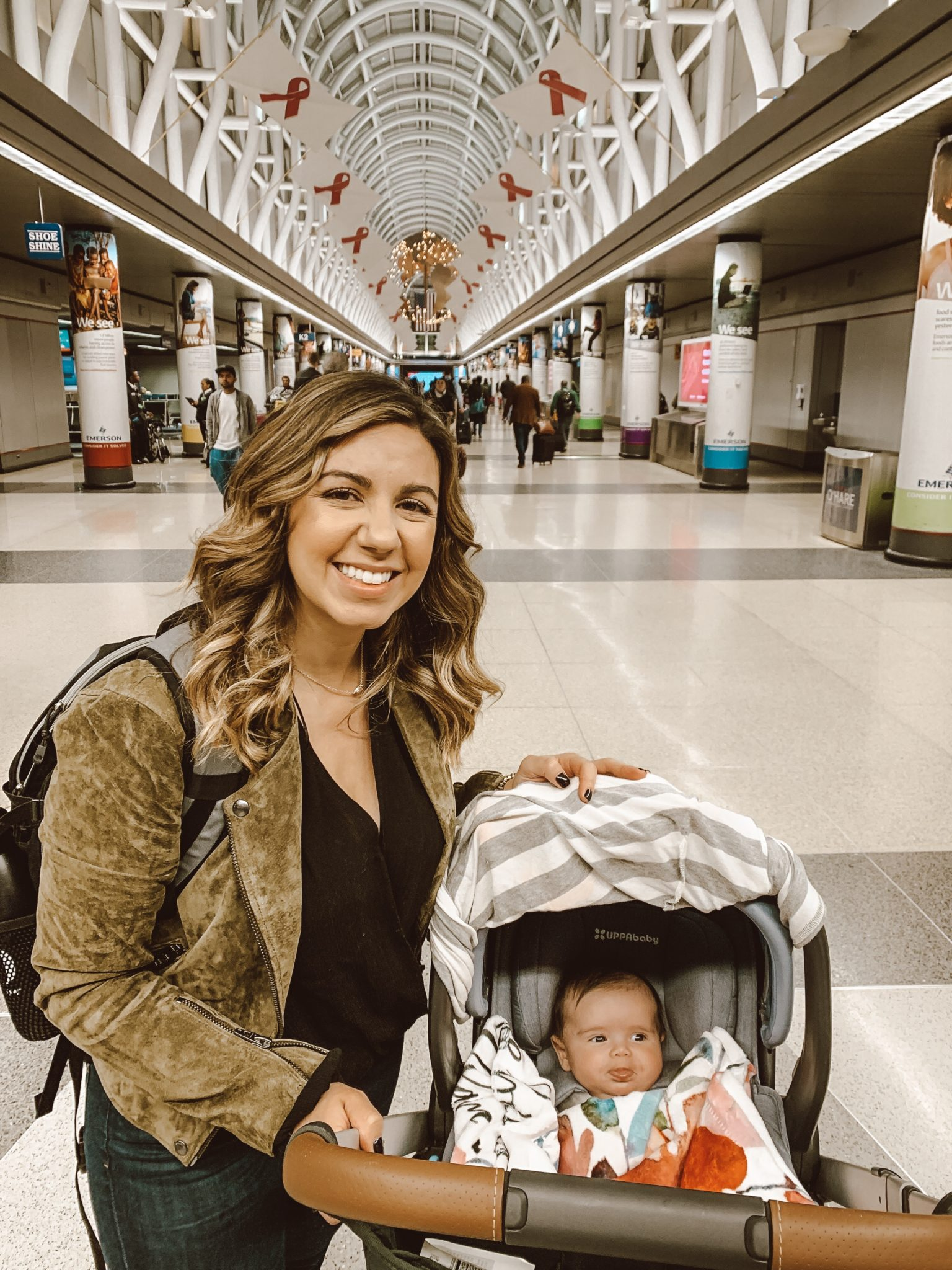 Essential Winter Packing List for Baby by popular Chicago lifestyle blog, Glass of Glam: image of a mom standing next to her baby stroller in a mall.