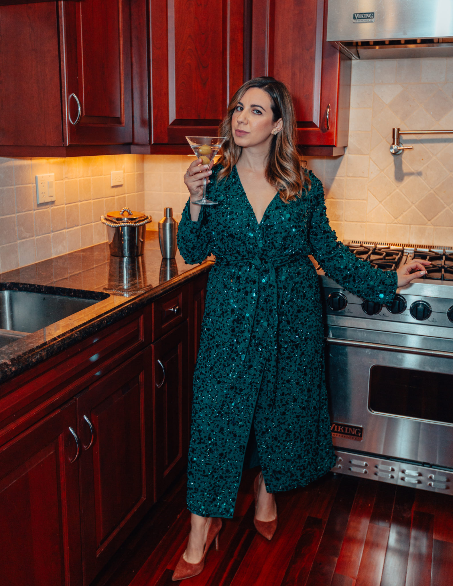 Gifts For Beverage Lovers by popular Chicago life and style blog, Glass of Glam: image of a woman wearing a green sequin dress and holding a martini glass in her kitchen.