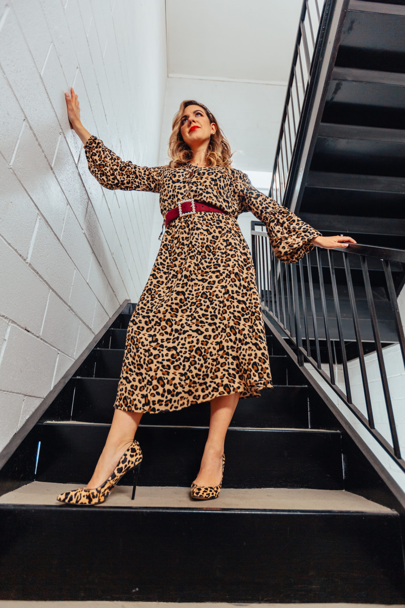 How Leopard Fashion Released Me From A Creative Slump by popular Chicago fashion blog, Glass of Glam: image of a woman standing in a stairwell and wearing a SheIn Leopard Print Half Button Blouson Shirt Dress, Nordstrom Sam Edelman Margie Genuine Calf Hair Pump, Amazon Kwartz Red Green Stripe Headbands with Leopard Print, and Amazon RangYR Women's fashion accessories belt inlaid pearl square buckle.