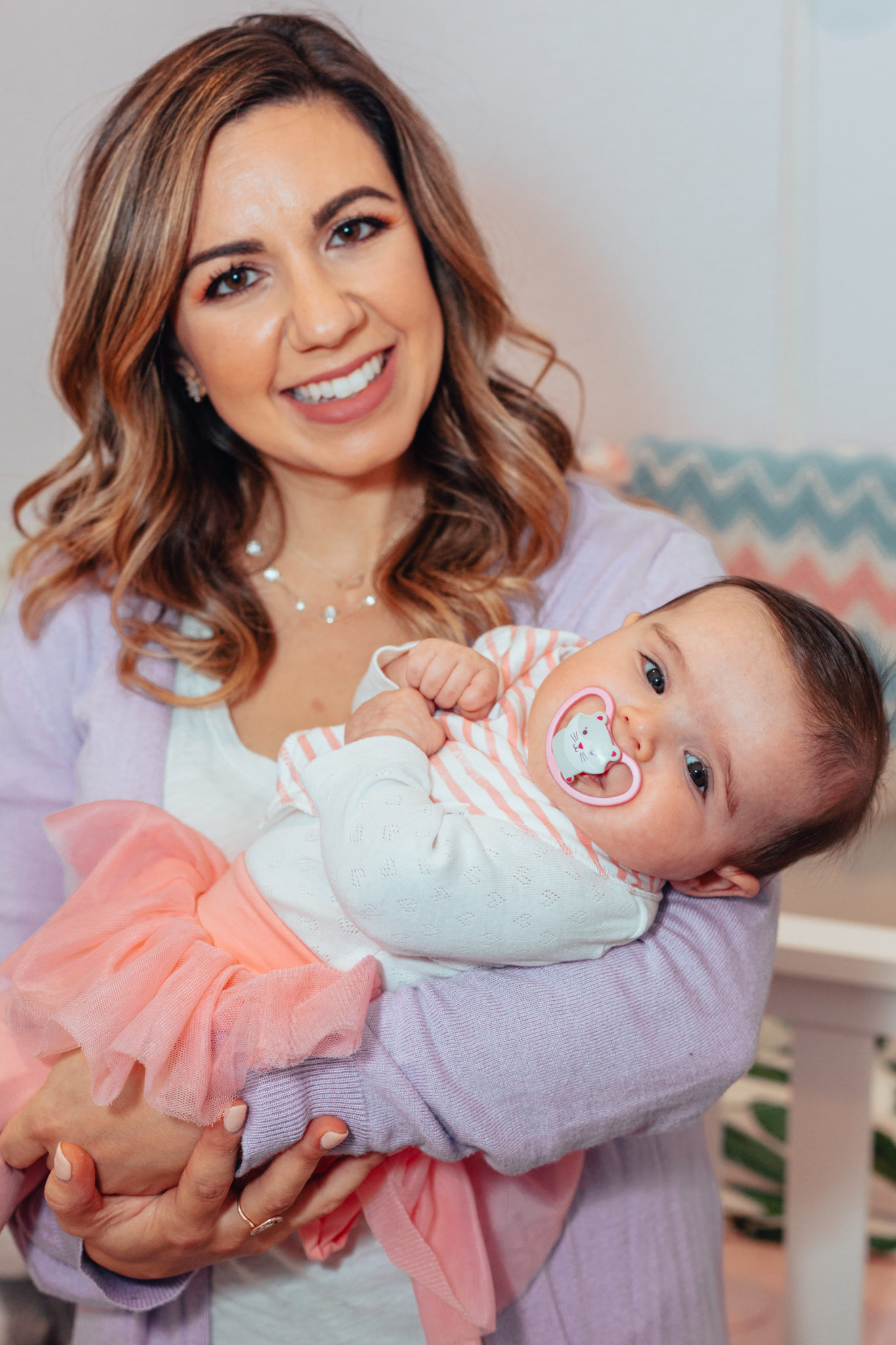 Amazing Gifts for New Moms by popular Chicago life and style blog, Glass of Glam: image of a mom holding a baby wearing a Gap Baby Tulle Skirt Legging Duo.