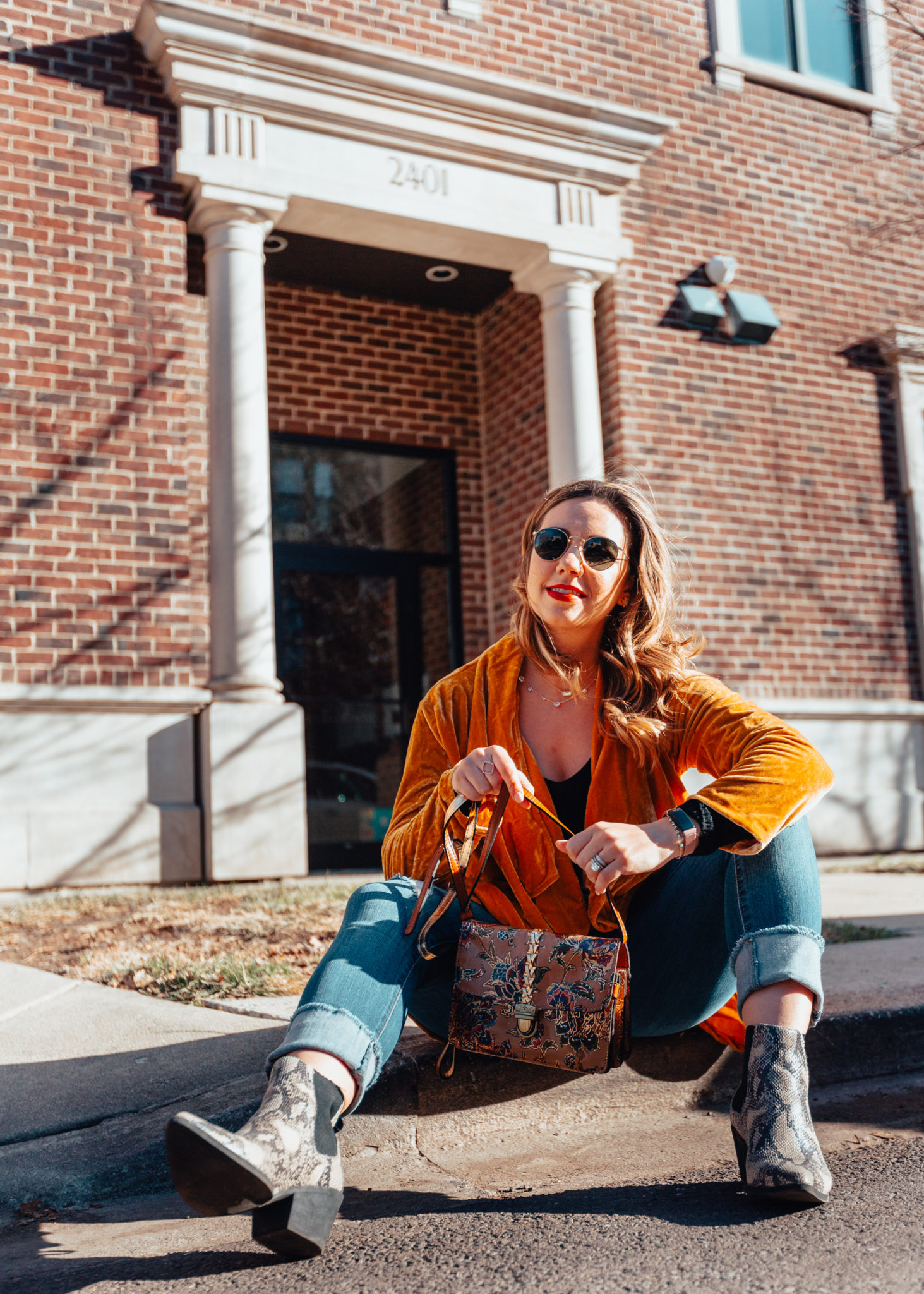 Patricia Nash Designs: An Accessories Brand That She Will Love! by popular Chicago fashion blog, Glass of Glam: image of a woman sitting outside and wearing an Amaryllis Draped in Velvet Cardigan, Nordstrom Ray-Ban Icons 53mm Retro Sunglasses, Target SUGARFIX by BaubleBar Druzy Stud Earring, 1822 Denim Taylor Destructed Roll Cuff Crop Jeans In Gerard, Sephora LANCÔME L'Absolu Rouge Lipstick, and holding a Patricia Nash French Tapestry Bianco Leather Crossbody.