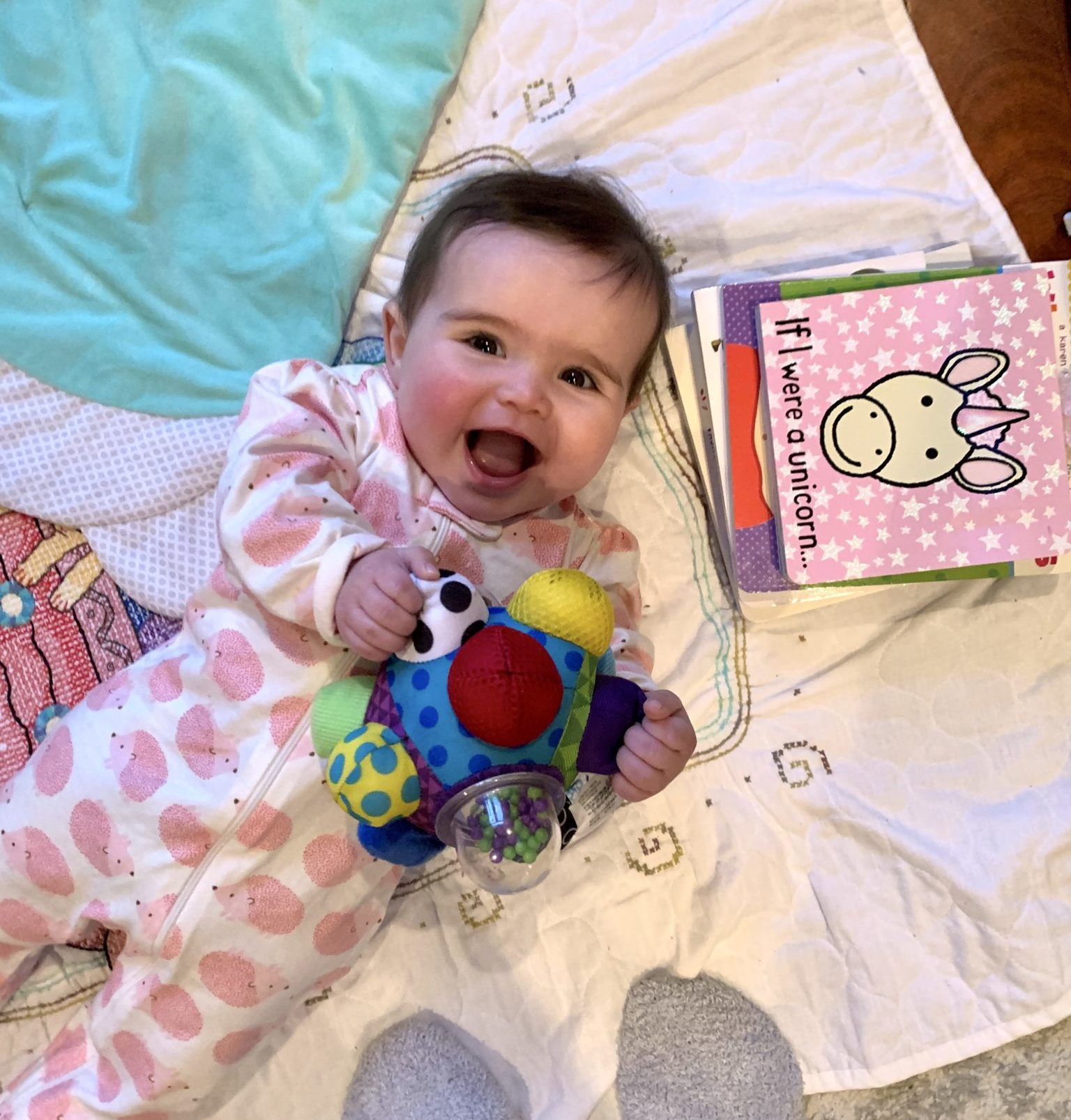 6 Month Old Baby Must Haves by popular Chicago lifestyle blog, Glass of Glam: image of a baby laying on a blanket on the floor and holding a sensory toy.