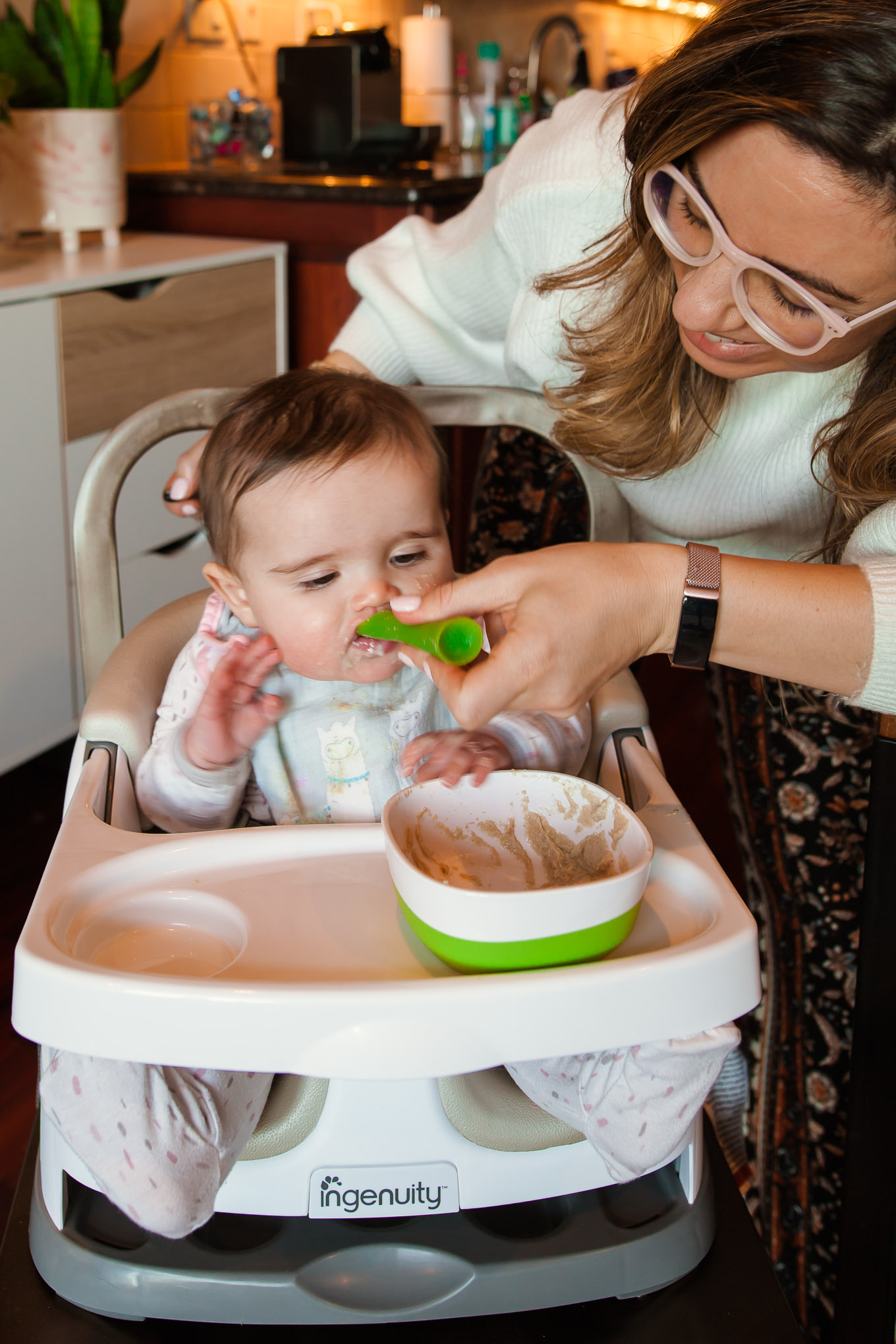 Ingenuity Baby Seat by popular Chicago mommy blog, Glass of Glam: image of a baby sitting in a Ingenuity baby seat and being fed food by her mom.