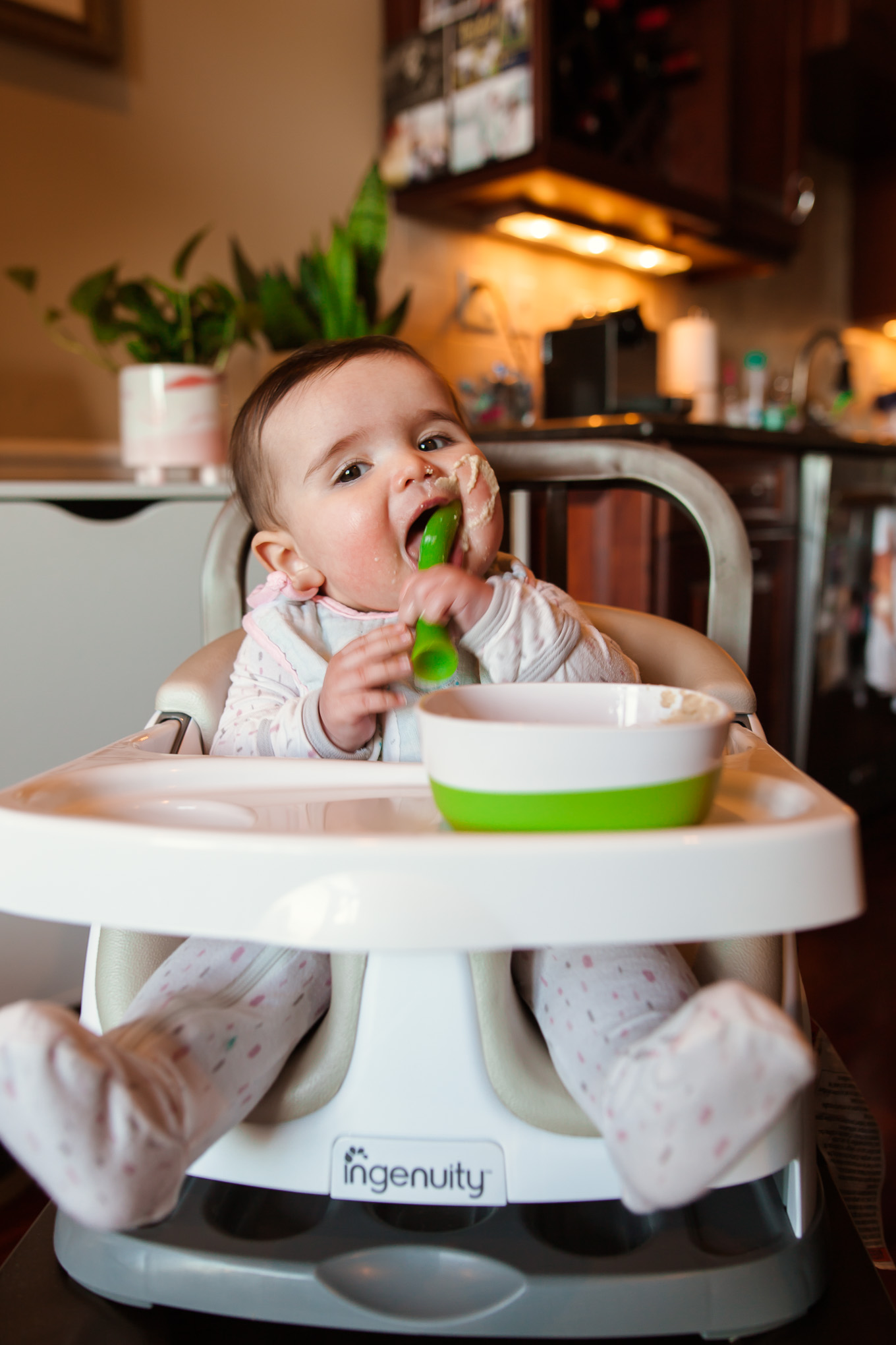 Ingenuity Baby Seat by popular Chicago mommy blog, Glass of Glam: image of a baby sitting in a Ingenuity baby seat and eating baby cereal.