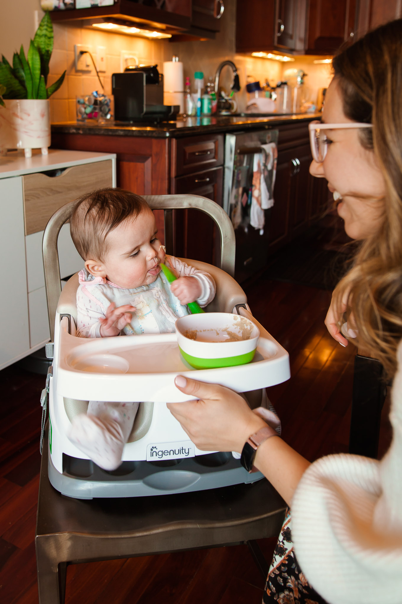 Ingenuity Baby Seat by popular Chicago mommy blog, Glass of Glam: image of a baby sitting in a Ingenuity baby seat and eating food.