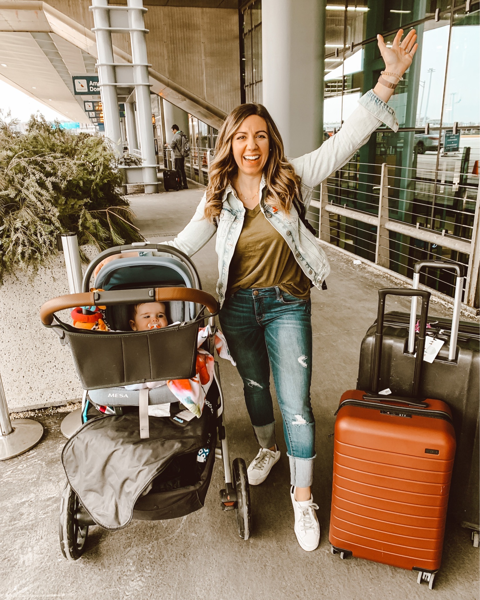 Shopbop Sale by popular Chicago fashion blog, Glass of Glam: image of a woman standing at an airport terminal with her luggage and her baby in a stroller.