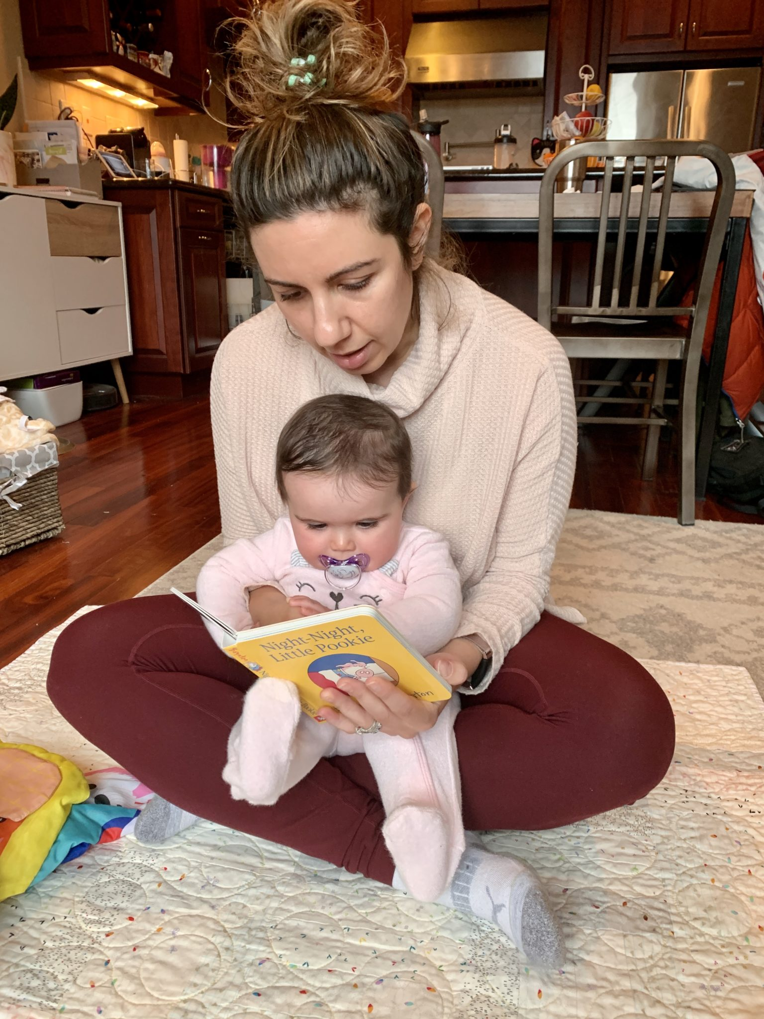 Best Baby Books by popular Chicago lifestyle blog, Glass of Glam: image of a mom sitting on the floor with her baby and reading Night Night Little Pookie.