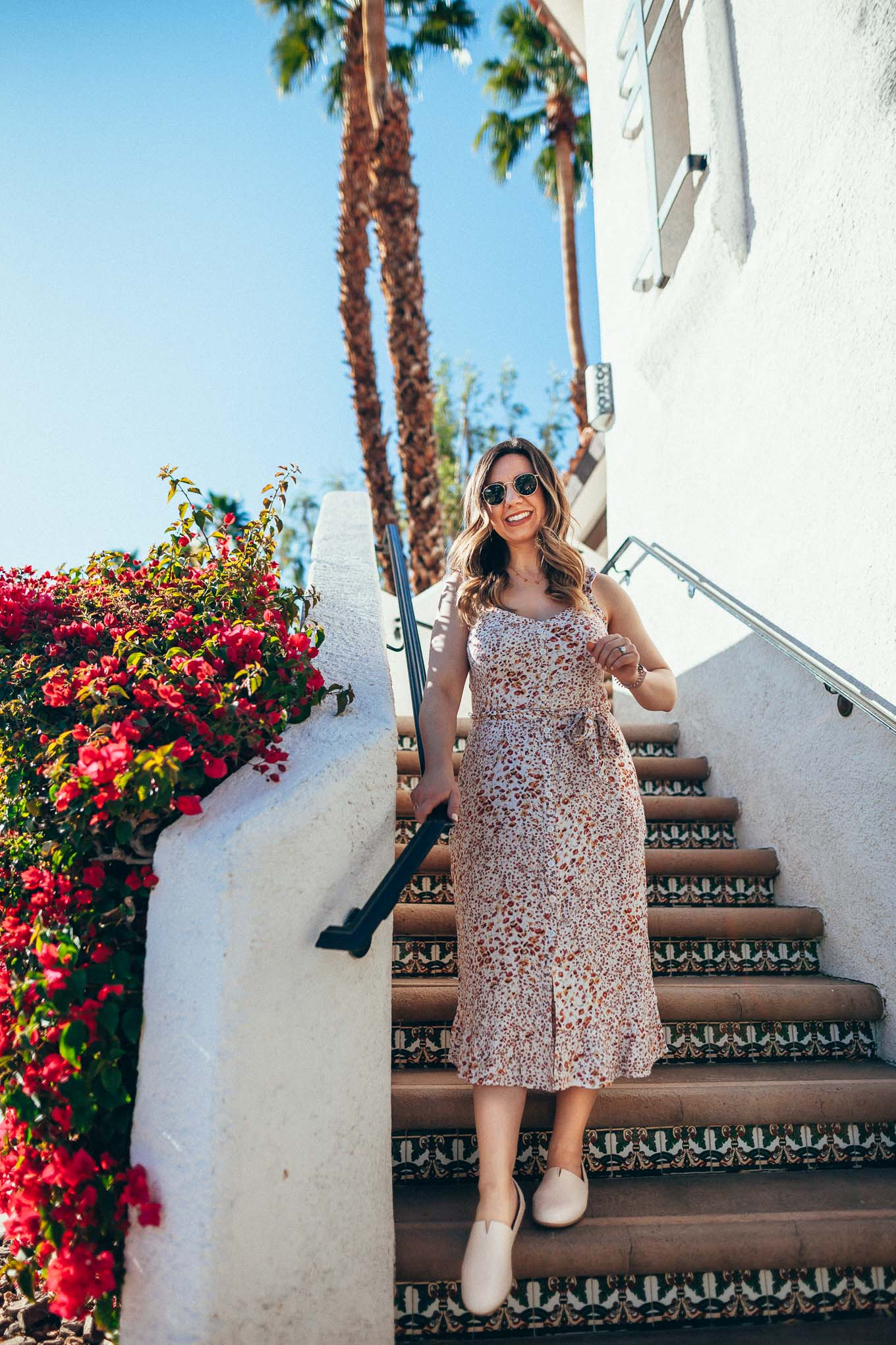 Boc Flats by popular Chicago fashion blog, Glass of Glam: image of a woman on a Spanish tile staircase and wearing a floral sleeveless dress and SUREE SLIP-ON. | Palm Springs Outfits by popular Chicago fashion blog, Just Add Glam: image of a woman standing on some Spanish tile steps and wearing a A&F Ruffle Midi Dress, DSW SUREE SLIP-ON, and Nordstrom Icons 53mm Retro Sunglasses RAY-BAN.
