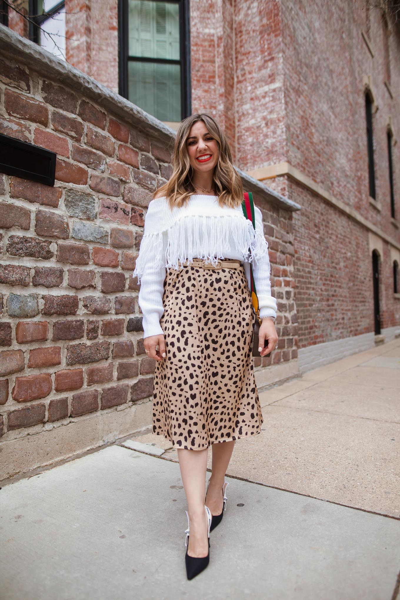 $30 Amazon Leopard Skirt by popular Chicago blog, Glass of Glam: image of a woman standing outside by a brick building and wearing a Amazon Ru Sweet Women's Off Shoulder Long Sleeve Slim Fit Fringe Knit Crop Top Sweater, Amazon Keasmto Leopard Midi Skirt Plus Size for Women, Dior J'ADIOR PUMP IN TECHNICAL CANVAS, Gucci Neo Vintage GG Supreme messenger bag, and Target Revlon Super Lustrous The Luscious Mattes Lipstick.