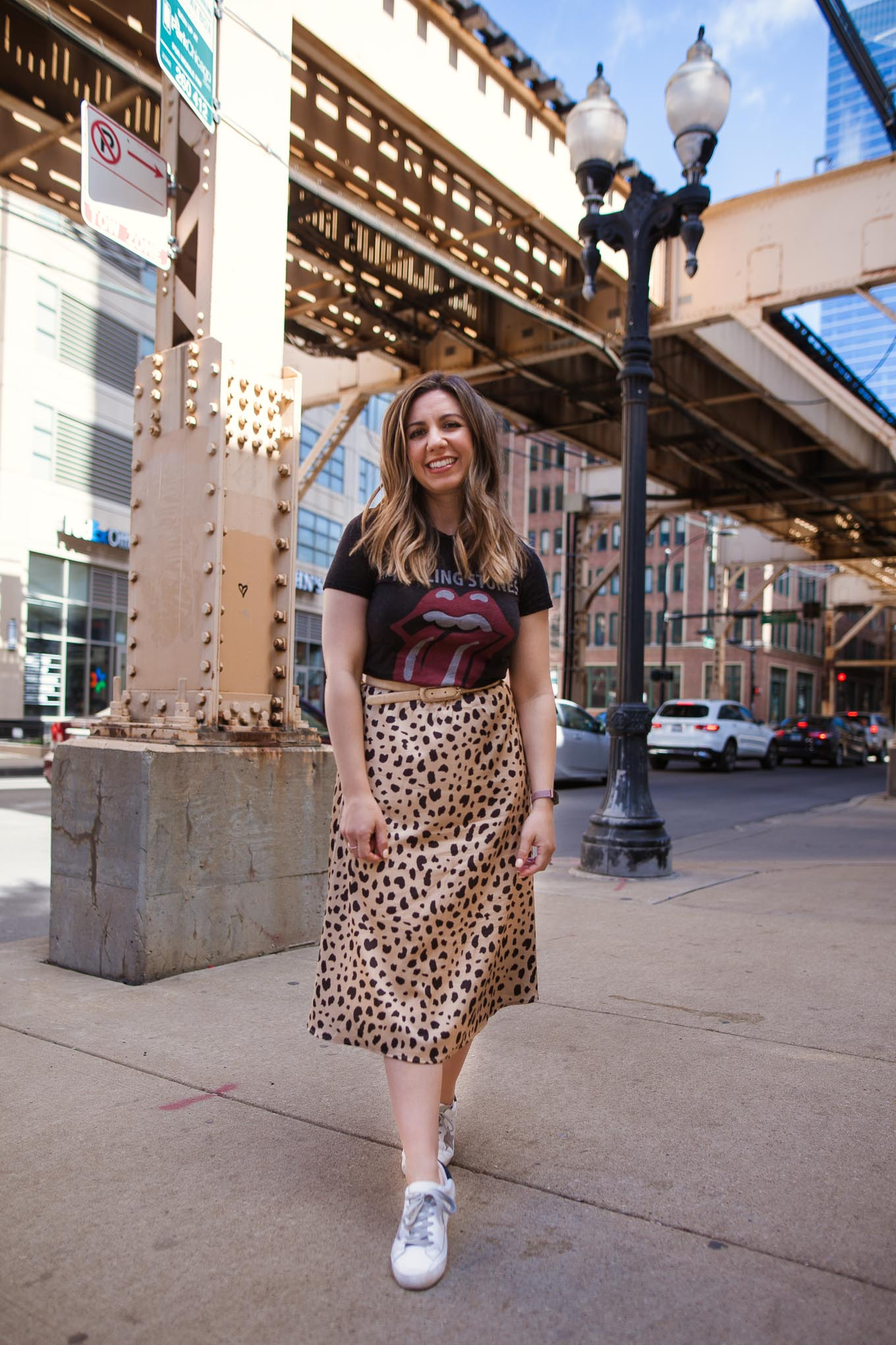 $30 Amazon Leopard Skirt by popular Chicago blog, Glass of Glam: image of a woman standing outside by a brick building and wearing a Amazon Keasmto Leopard Midi Skirt Plus Size for Women, Target Women's The Rolling Stones Short Sleeve Graphic T-Shirt, SheIn Star Patch Lace Up Splice Sneakers, and Target Revlon Super Lustrous The Luscious Mattes Lipstick.