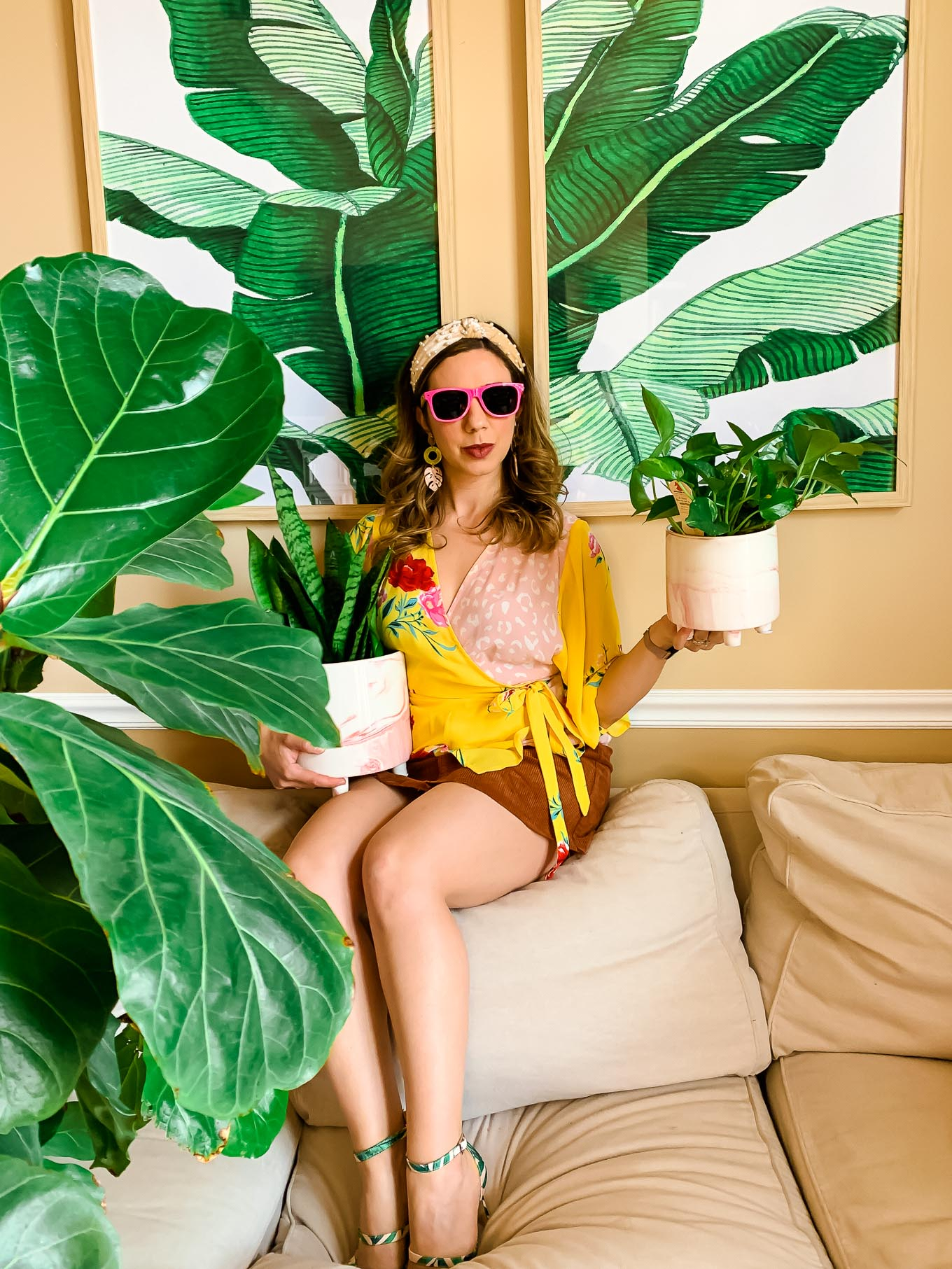 Hard to Kill House Plants by popular Chicago lifestyle blog, Glass of Glam: image of a woman sitting on a leather couch next to a fiddle leaf fig tree and palm frond prints while holding a Wayfair 2-Piece Ceramic Pot Planter Set.