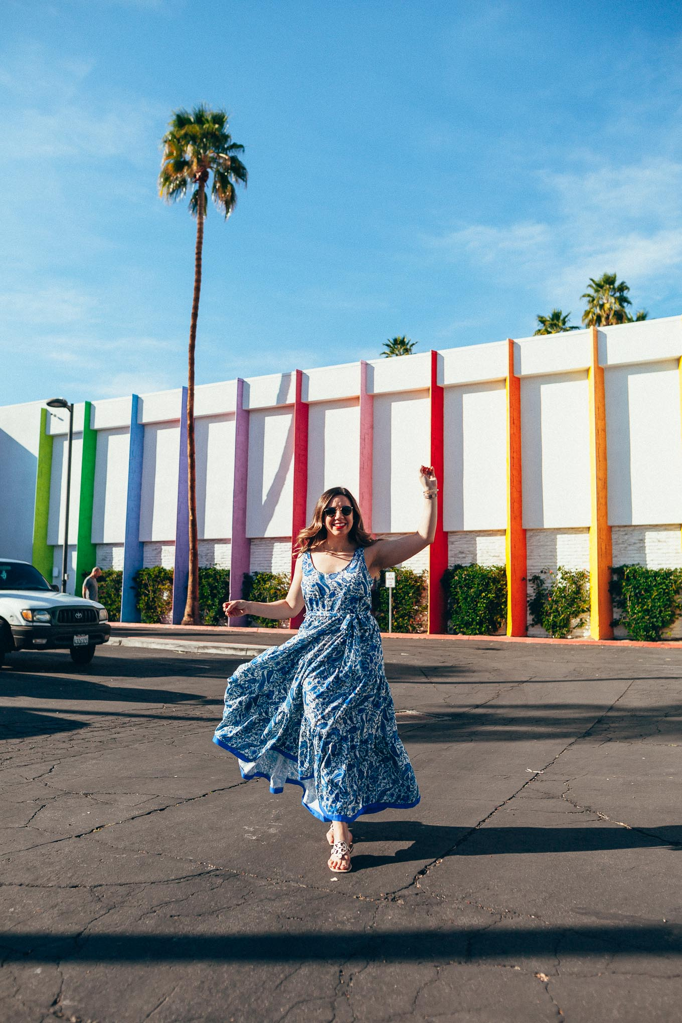 Palm Springs Outfits by popular Chicago fashion blog, Just Add Glam: image of a woman standing in front of a rainbow colored hotel and wearing a Red Dress Noticing You Blue Multi Print Maxi Dress, Nordstrom Miller Flip Flop TORY BURCH, and Nordstrom Icons 53mm Retro Sunglasses RAY-BAN.