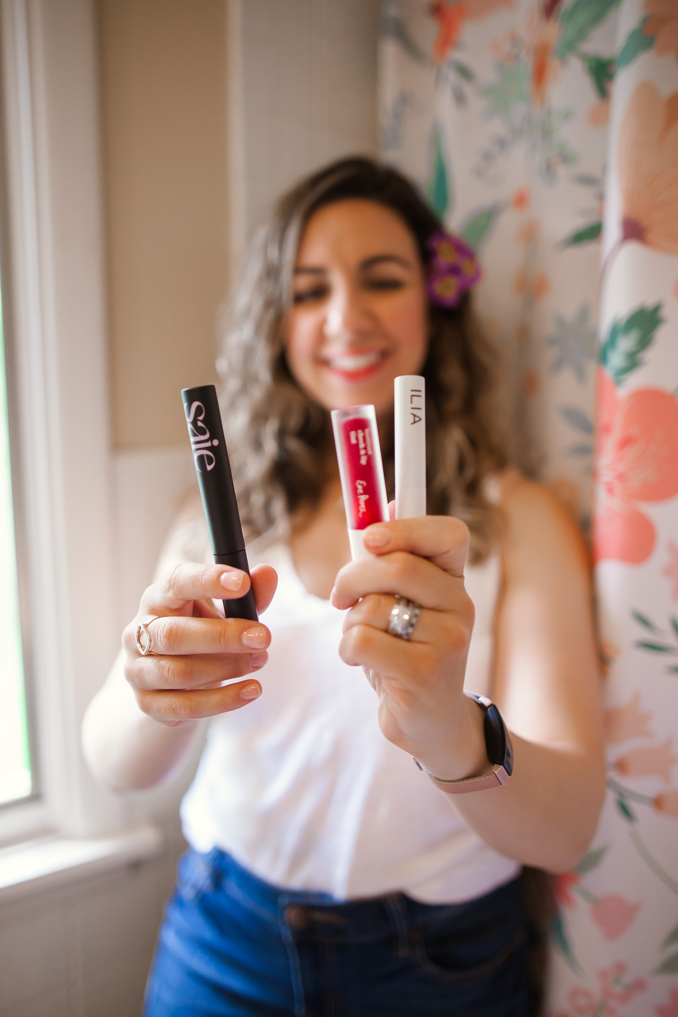 Clean Beauty by popular Chicago beauty blog, Glass of Glam: image of a woman in a white tank top and jeans and standing in front of a floral shower curtain while wearing RMS Beauty Un Cover-Up, Saie Mascara, Ere Perez Lip and Cheek Tint, RMS Beauty Lip2Cheek, Ilia Brow Gel, RMS Beauty Magic Luminizer