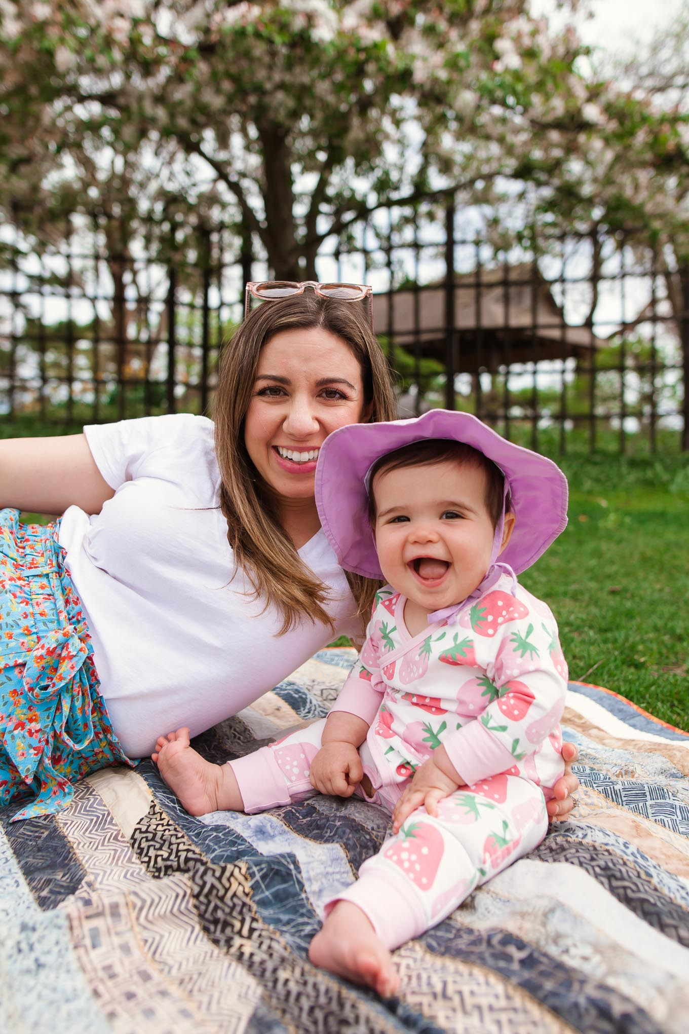 Picnic in the Park by popular Chicago lifestyle blog, Glass of Glam: image of a woman wearing Loft FLORAL TIE WAIST CARGO SHORTS, J. Crew V-neck cotton tee, SheIn Star Patch Lace Up Splice Sneakers, and WODISON WODISON Womens Retro Mirrored Sunglasses and holding her daughter who is wearing a Monica + Andy Kimono Tie One-Piece and green sprouts i play.® by green sprouts® Brim Sun Hat while laying on a blanket at the park.