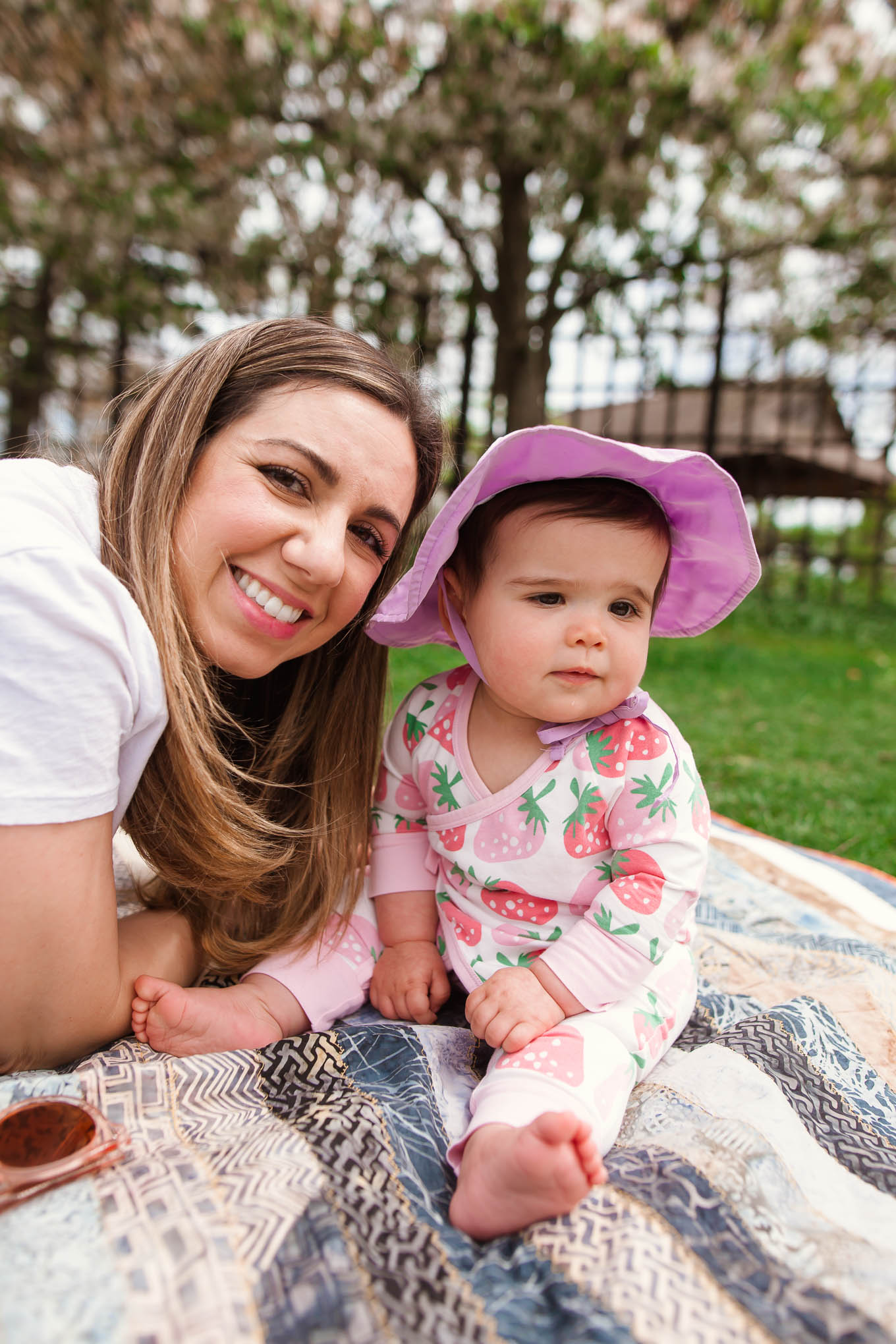 Picnic in the Park by popular Chicago lifestyle blog, Glass of Glam: image of a baby girl wearing a Monica + Andy Kimono Tie One-Piece and green sprouts i play.® by green sprouts® Brim Sun Hat while sitting on a blanket with her mom at the park.