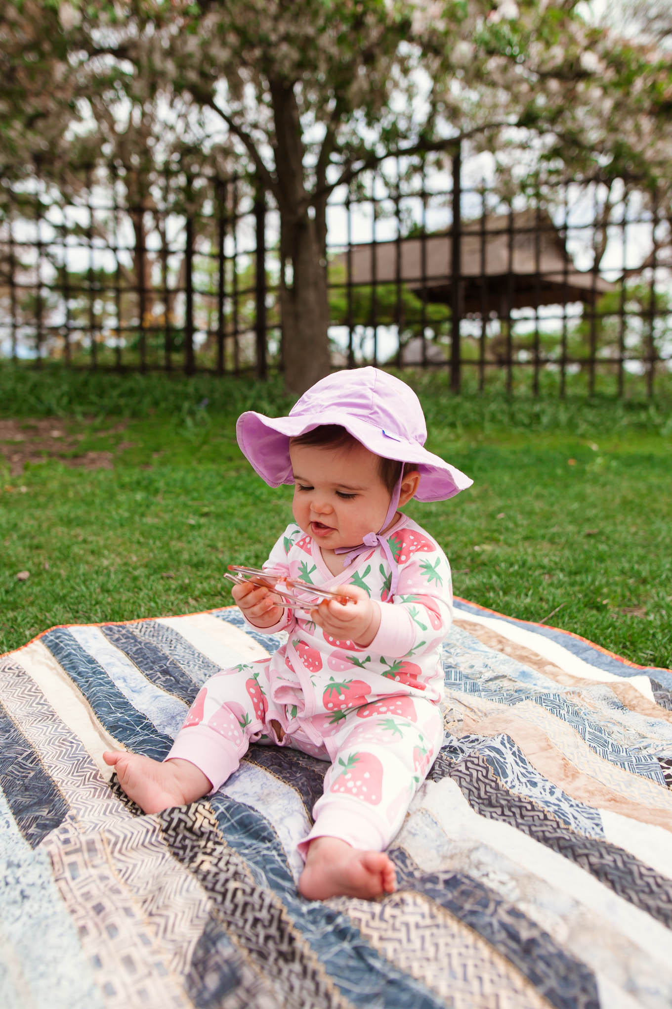 Picnic in the Park by popular Chicago lifestyle blog, Glass of Glam: image of a baby girl wearing a Monica + Andy Kimono Tie One-Piece and green sprouts i play.® by green sprouts® Brim Sun Hat while sitting on a blanket at the park.