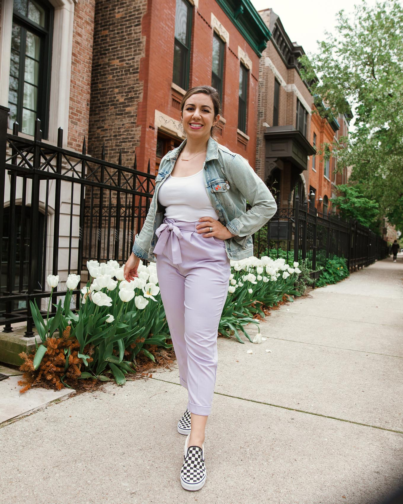 Tie Waist Pants by popular Chicago fashion blog, Glass of Glam: image of a woman standing outside by some white tulips and wearing a pair of lavender tie waist pants, Old Navy First-Layer Slim-Fit Rib-Knit Tank Top for Women, Old Navy Distressed Jean Jacket for Women, Nordstrom Classic Slip-On Sneaker VANS, and Kendra Scott Kelsey Pendant Necklace In Rose Gold.