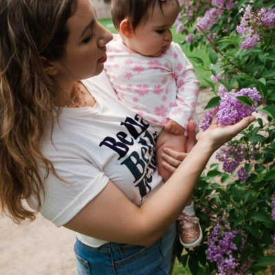 Link Up by popular Chicago lifestyle blog, Glass of Glam: image of a woman holding her baby while standing next to a lilac bush and wearing a Bella t-shirt, Abercrombie & Fitch High Rise Mom Shorts, Monica + Andy Long Sleeve Jack + Jill Bodysuit, and Keds Little Kid's Keds x kate spade new york Champion Glitter Crib Sneaker.