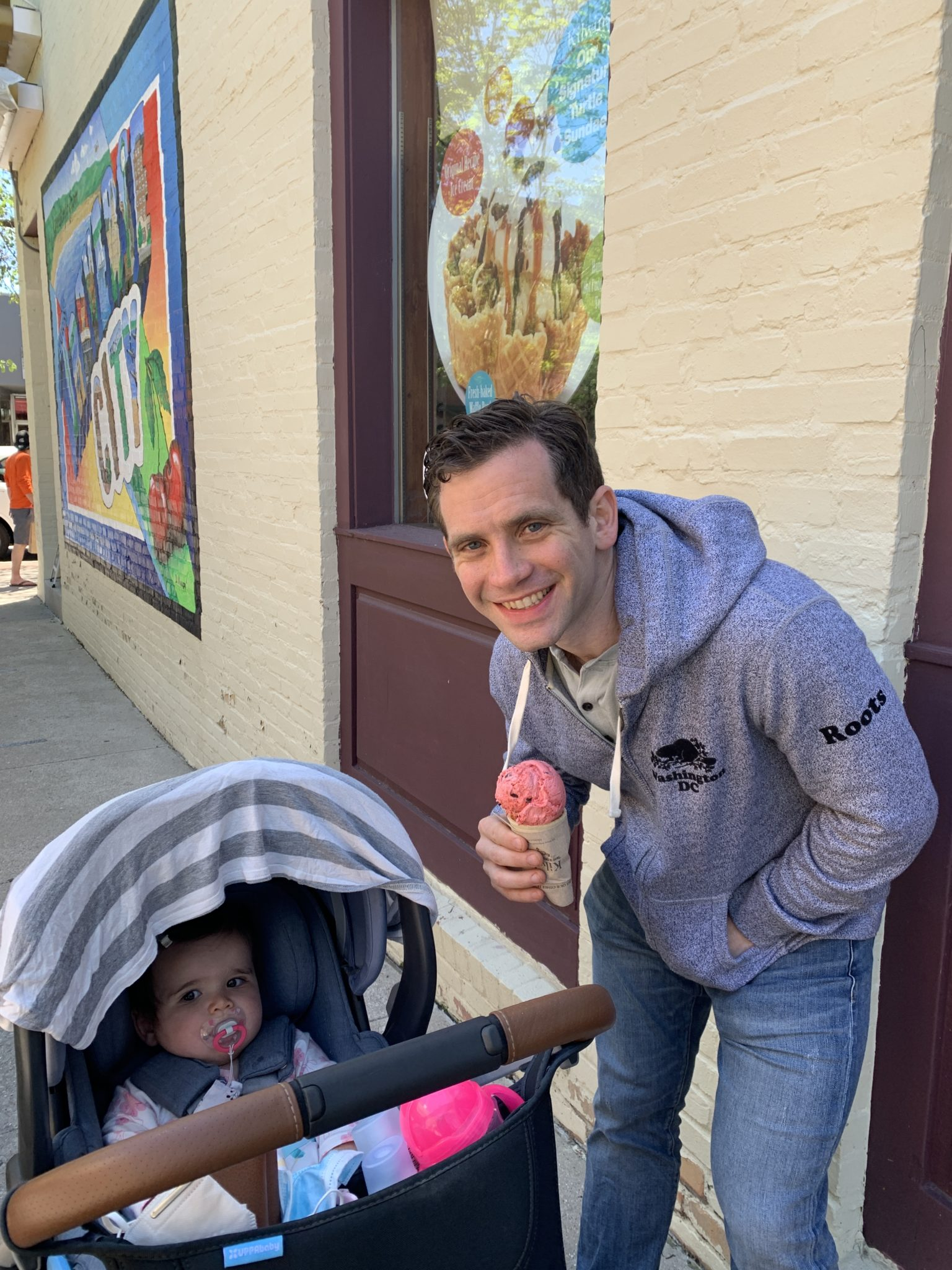 Traverse City by popular Chicago travel blog, Glass of Glam: image of a dad holding a ice cream cone and standing next to his baby daughter who's in a stroller.