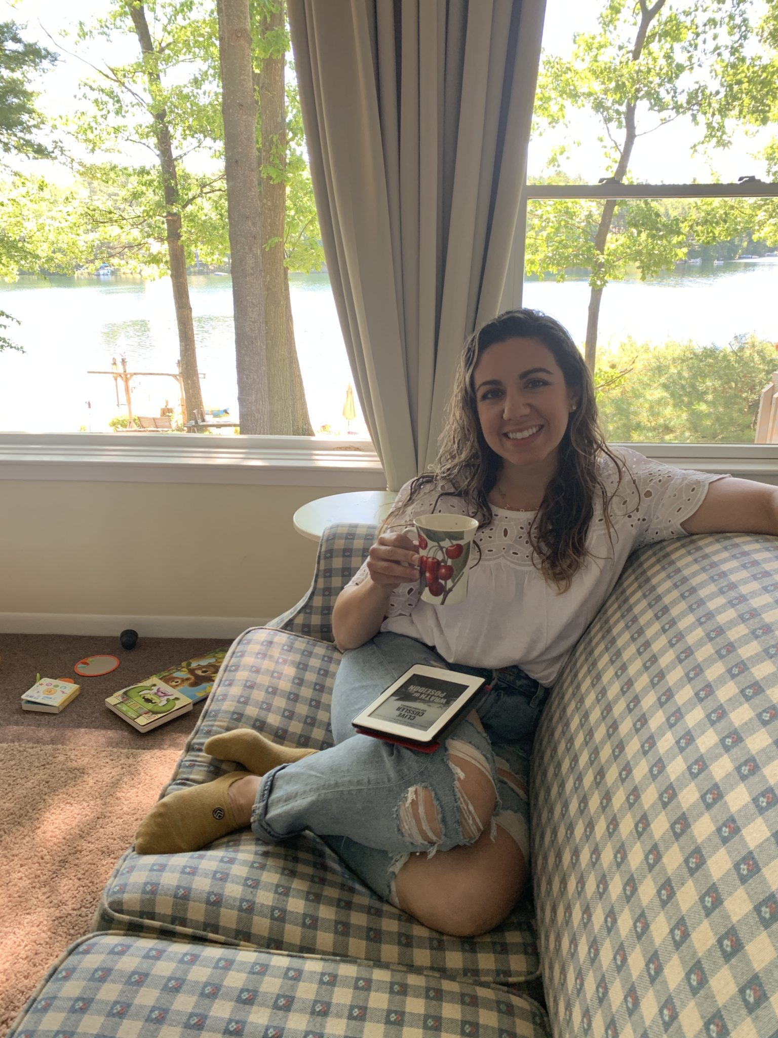 Traverse City by popular Chicago travel blog, Glass of Glam: image of a woman sitting on a couch and holding a coffee mug.