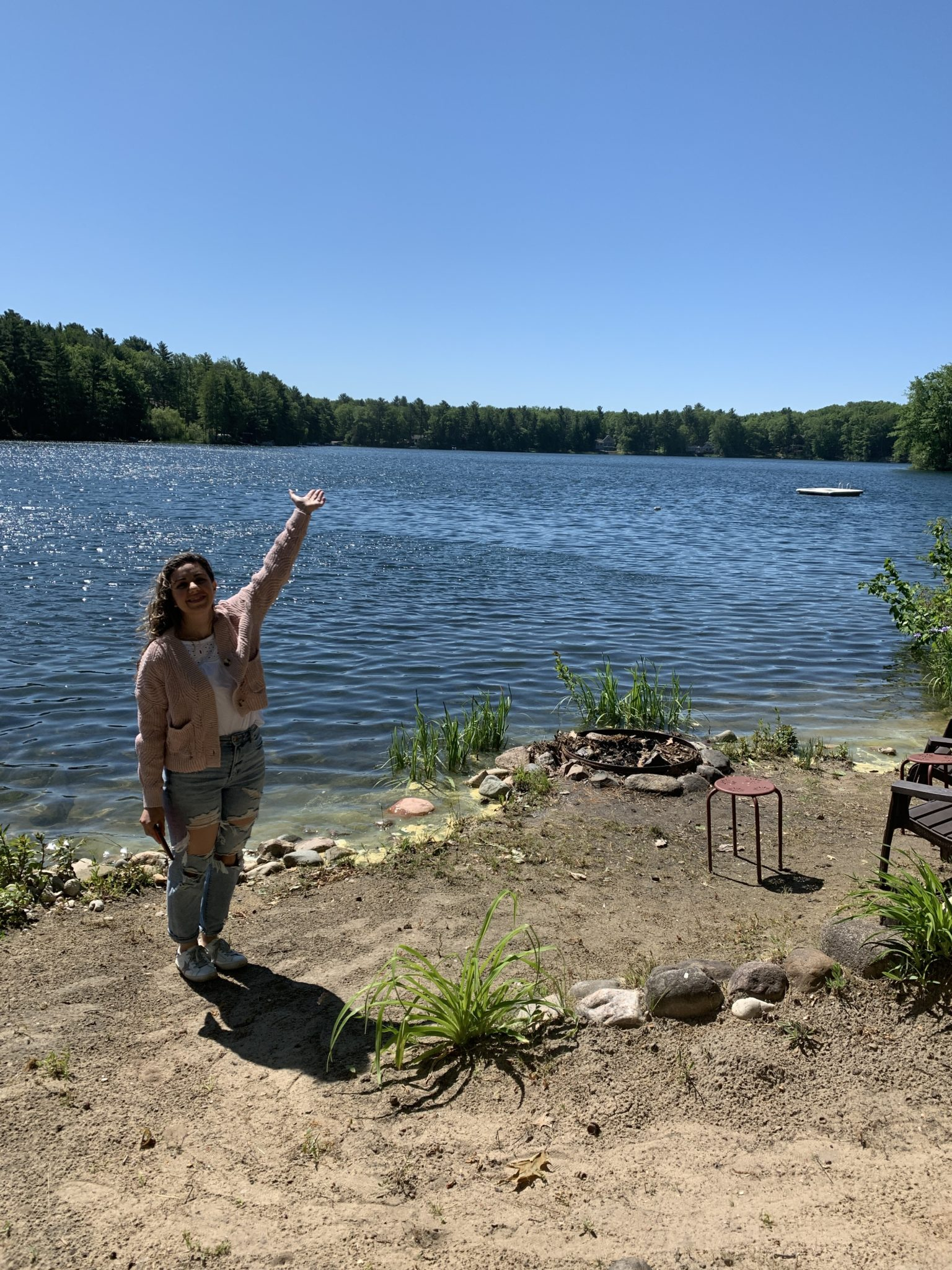 Traverse City by popular Chicago travel blog, Glass of Glam: image of a woman standing next to a lake.