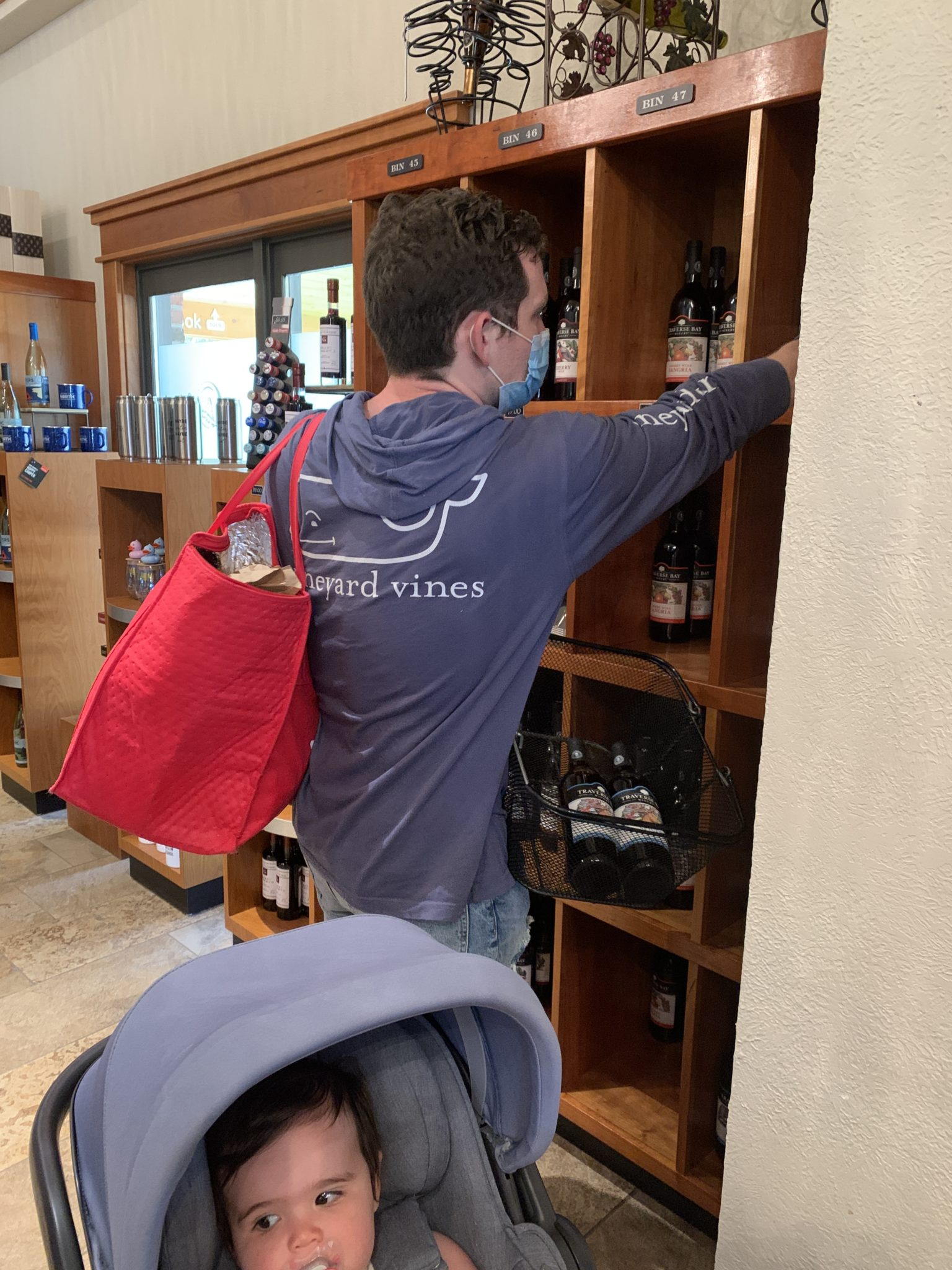 Traverse City by popular Chicago travel blog, Glass of Glam: image of a man reaching for a wine bottle.