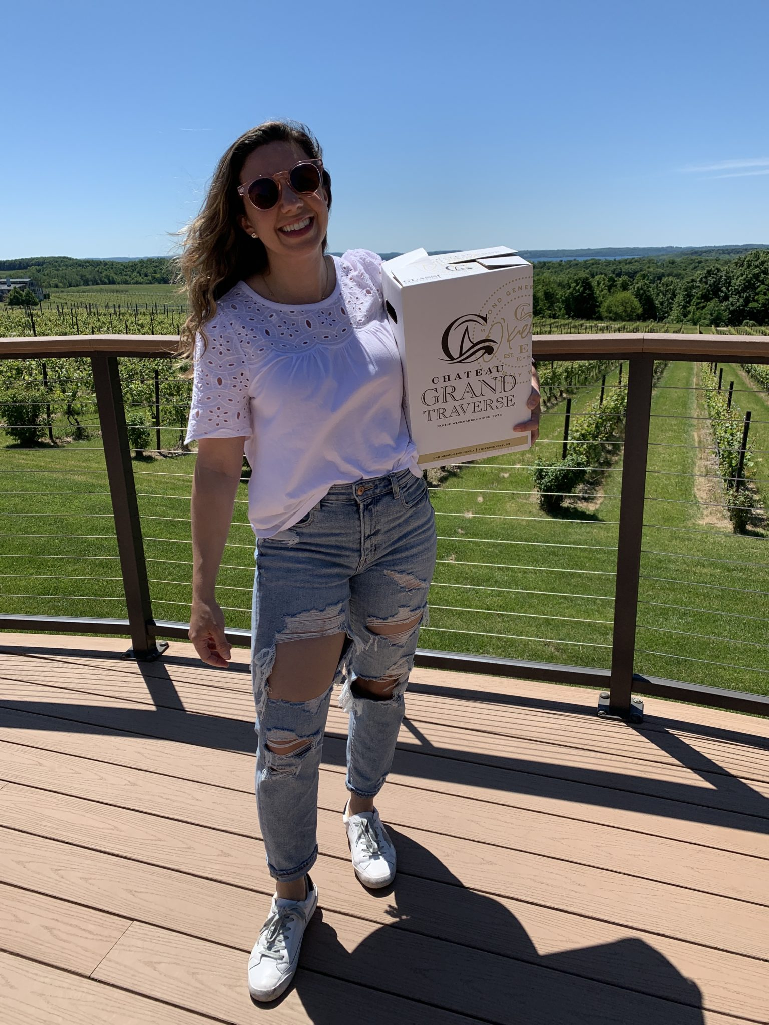 Traverse City by popular Chicago travel blog, Glass of Glam: image of a woman holding a box of wine.