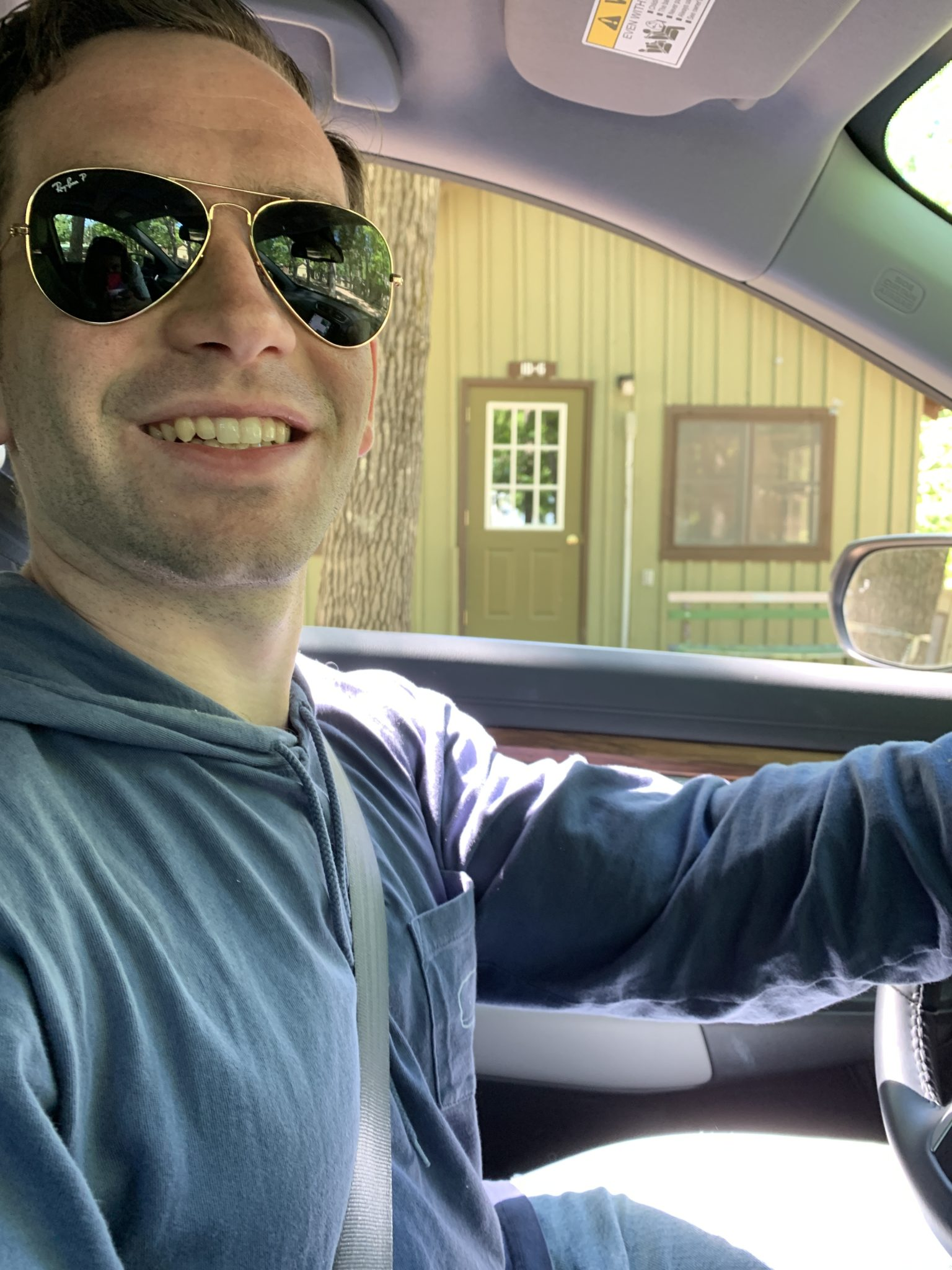 Traverse City by popular Chicago travel blog, Glass of Glam: image of a man wearing aviator sunglasses and driving a car.