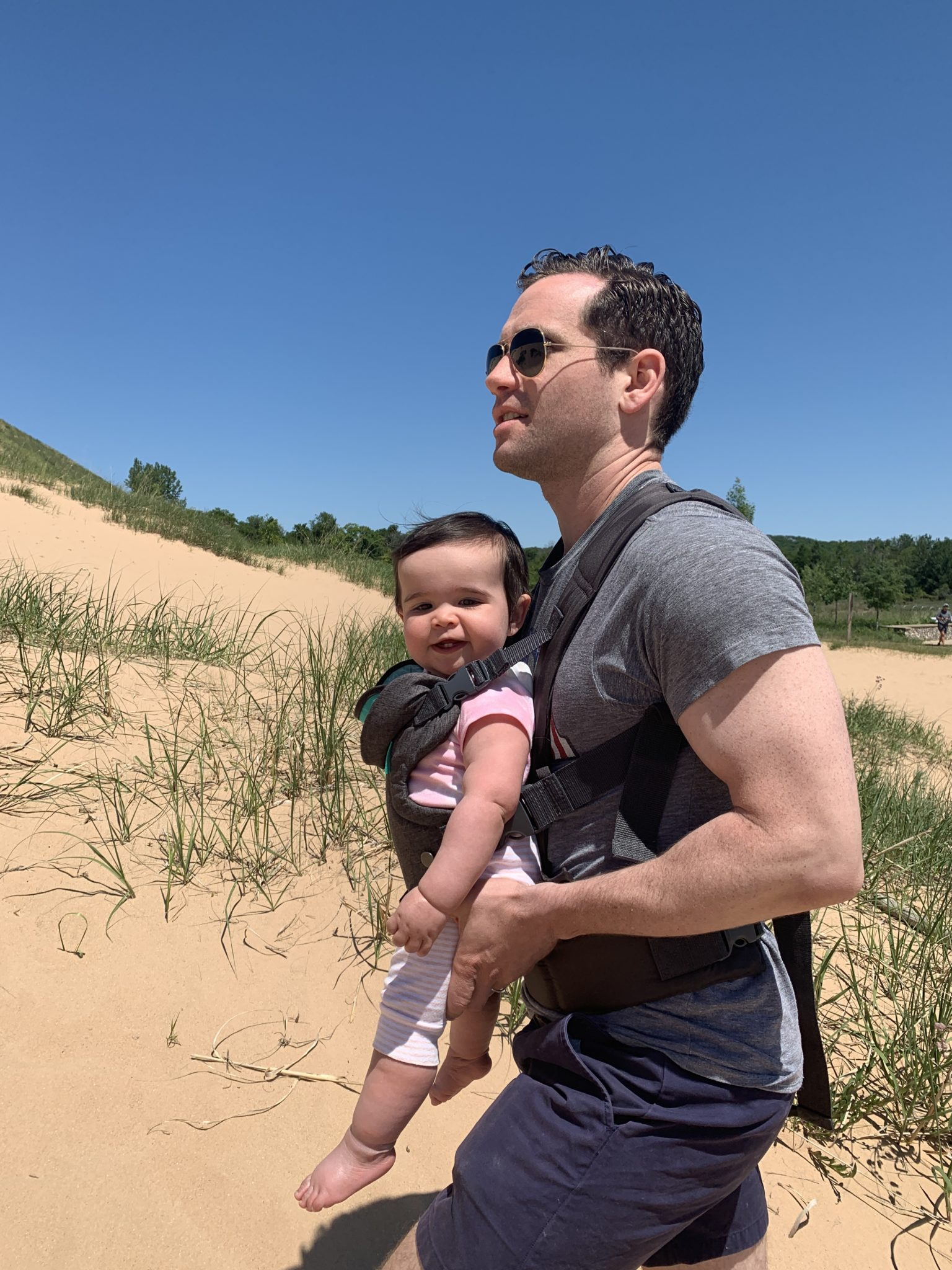 Traverse City by popular Chicago travel blog, Glass of Glam: image of a dad carrying his baby in a baby carrier while walking on a sand dune.