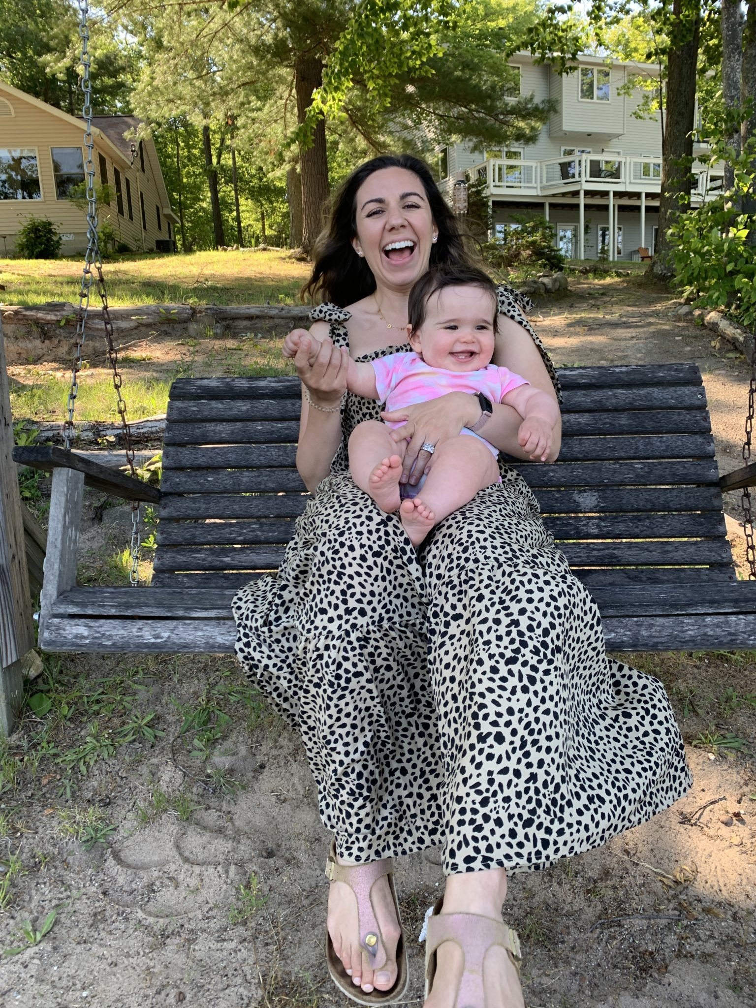 Traverse City by popular Chicago travel blog, Glass of Glam: image of a mom holding her baby daughter on a bench swing.