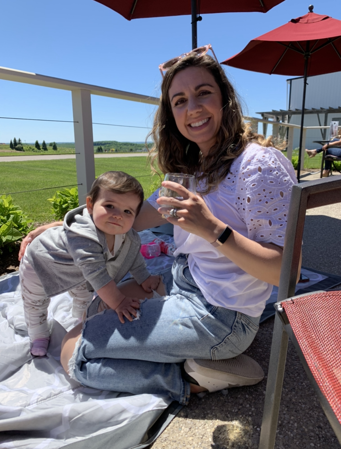Traverse City by popular Chicago travel blog, Glass of Glam: image of a mom and daughter sitting on the ground outside.