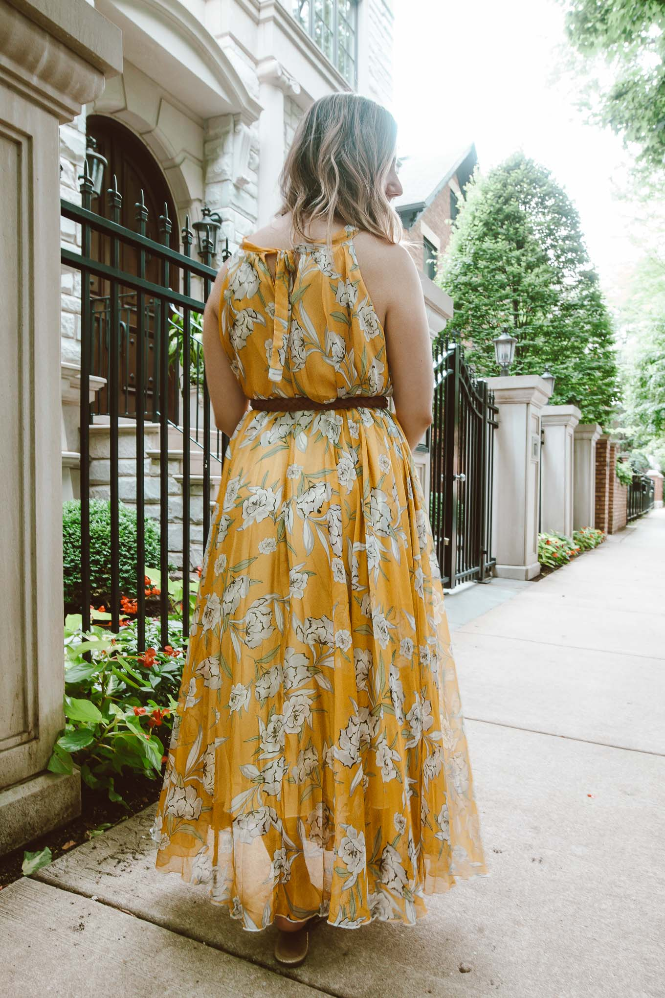 Yellow Dresses by popular Chicago fashion blog, Glass of Glam: image of a woman standing outside and wearing a Chicwish yellow floral maxi dress, thrifted braided belt, and Nordstrom Miller Flip Flop TORY BURCH.