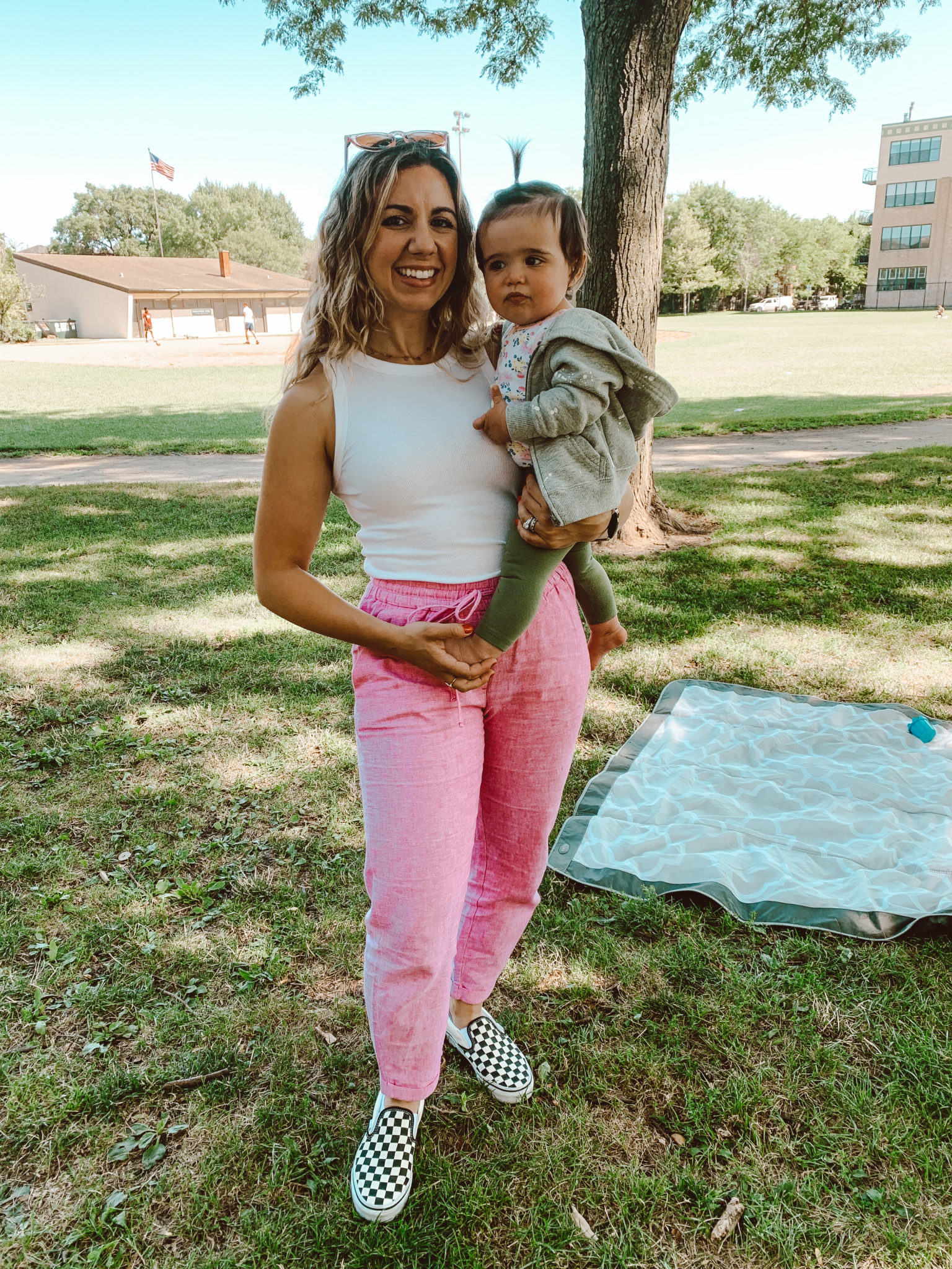 Linen Pants by popular Chicago fashion blog, Glass of Glam: image of a woman holding her baby daughter at a park and wearing a J. Crew LINEN-COTTON DRAWSTRING PANT, Target A New Day Women's Tank Top, and Nordstrom Classic Slip-On Sneaker VANS.