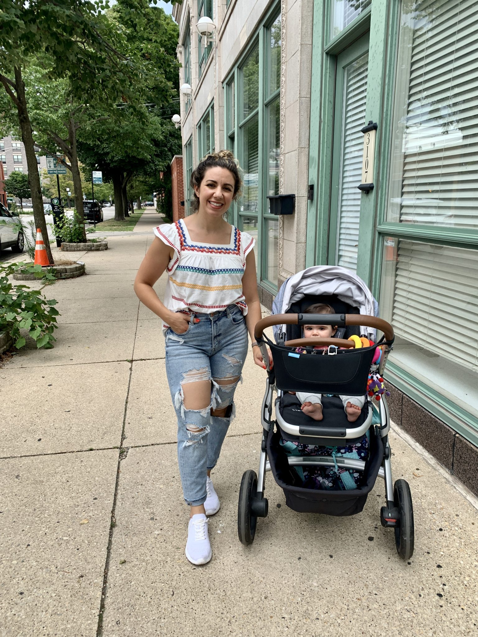 Embroidered Top by popular Chicago fashion blog, Glass of Glam: image of a woman standing next to a baby stroller on a city sidewalk and wearing a Going With You White Multi Top THML, AE Mom Jean, and SheIn CUCCOO - The Everyday Sneakers.