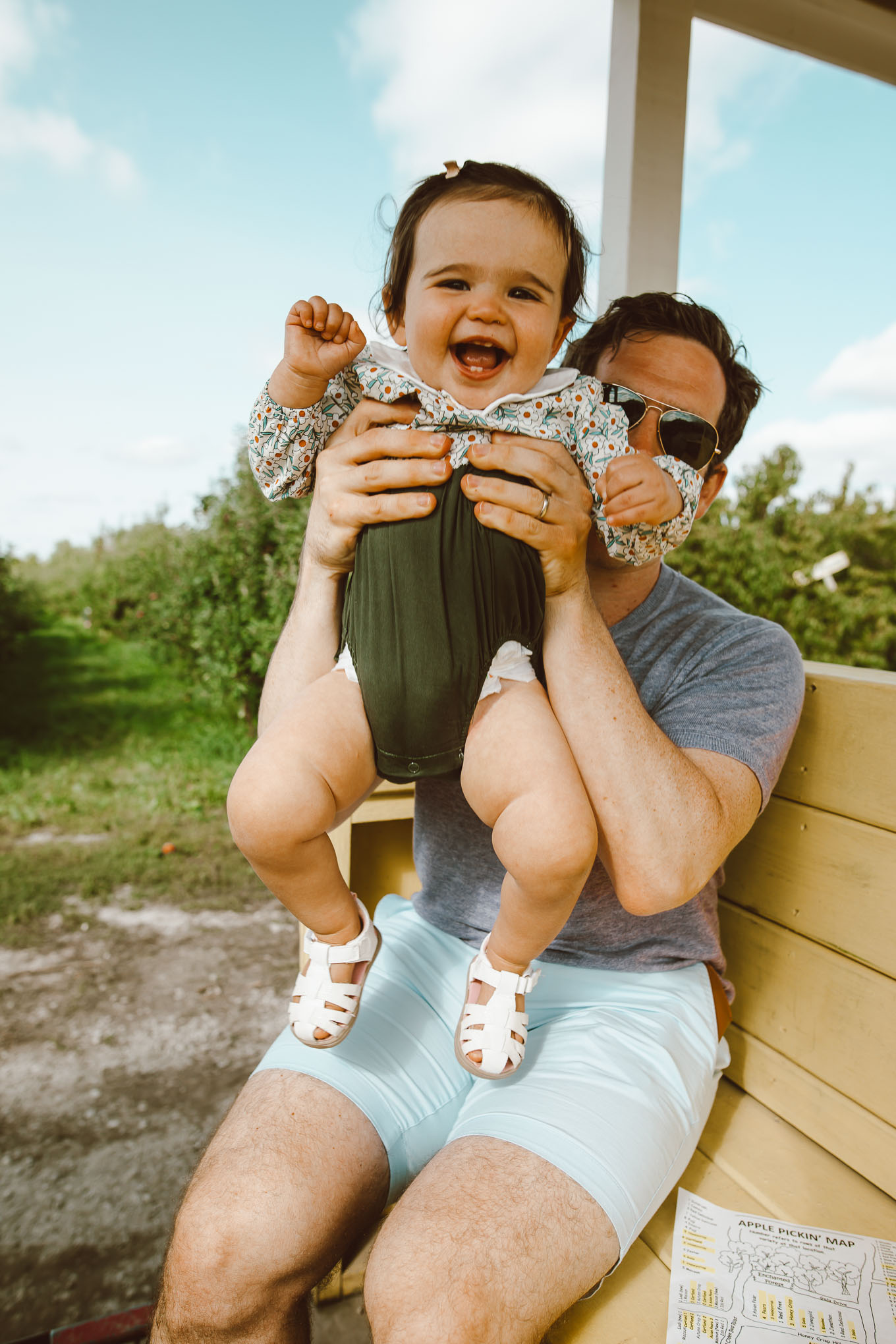 Apple Picking by popular Chicago lifestyle blog, Glass of Glam: image of a dad sitting on a bench and holding his 1 year old daughter that is wearing a Amazon Simplee Kids store romper.