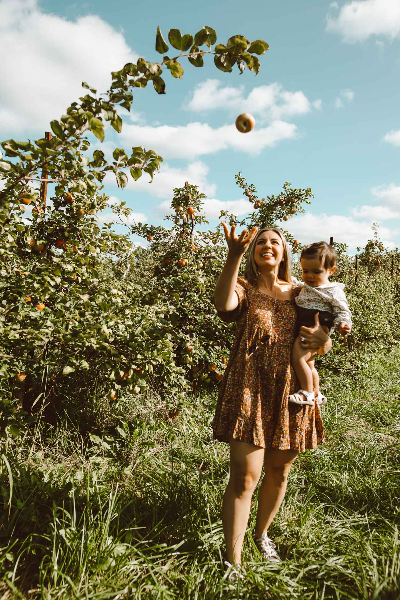 Apple Picking by popular Chicago lifestyle blog, Glass of Glam: image of a woman and her 1 year old daughter in a apple orchard and wearing a Target Women's Puff Short Sleeve Dress, Zappos Converse Chuck Taylor® All Star® Core Ox, and Amazon Simplee kids Baby Girl Romper.