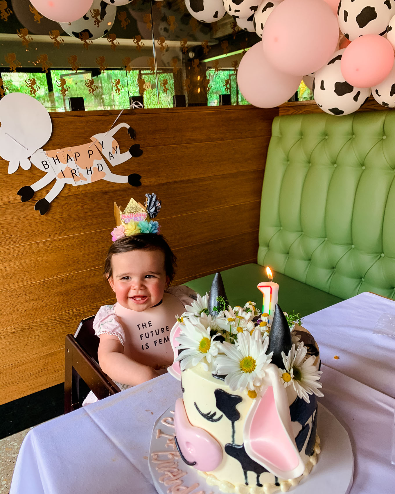 1st Birthday by popular Chicago lifestyle blog, Glass of Glam: image of a 1 year old baby girl wearing a birthday crown head band, the future is female bib, and sitting in a high chair next to a Amazon QIYNAO White and Blacke Dairy Cow Happy Birthday Banner, Amazon Finypa Funny Cow Party Decorations Balloon 85pcs Arch Garland, and ECGB Cake Studio cow birthday cake.