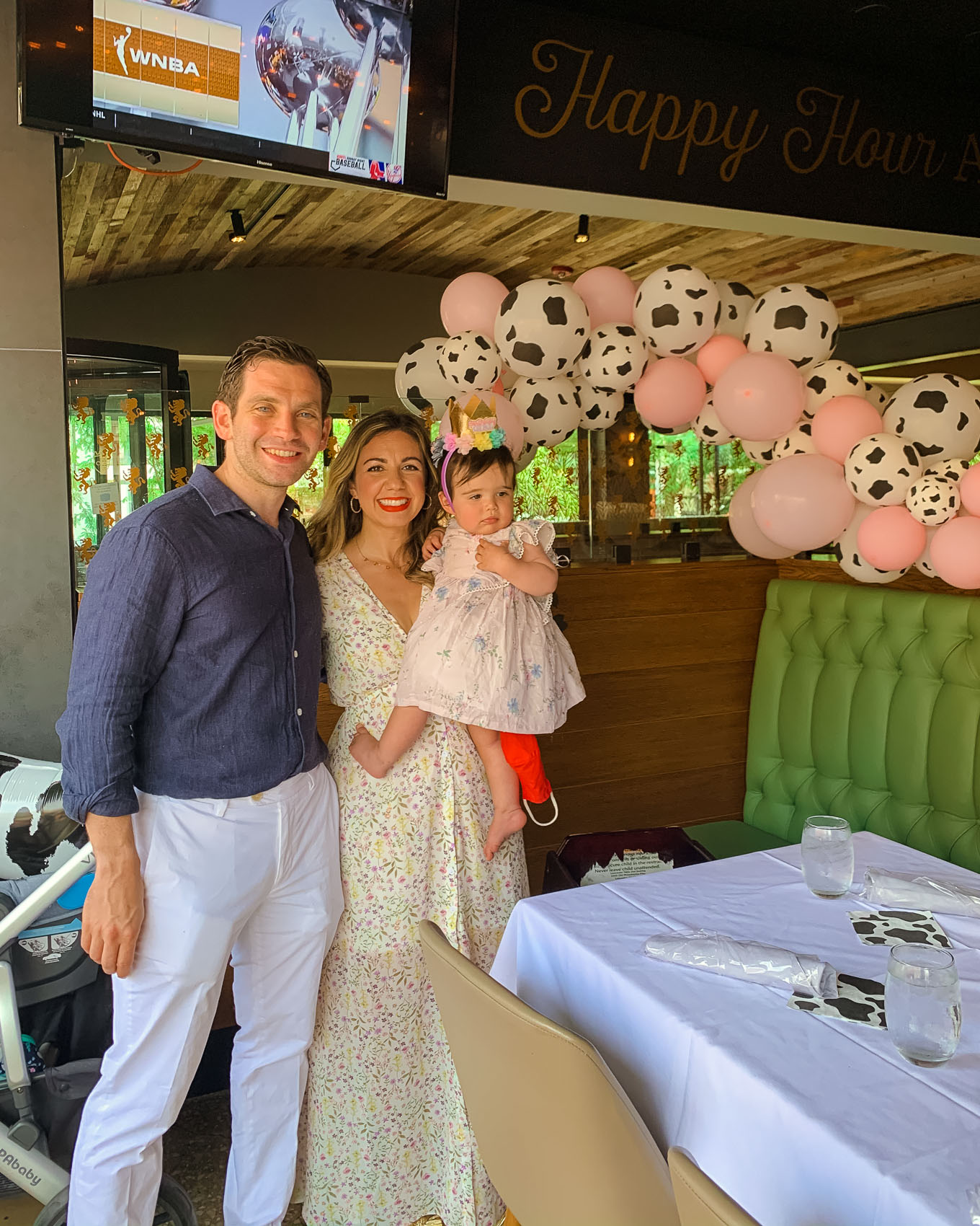 1st Birthday by popular Chicago lifestyle blog, Glass of Glam: image of a Mom and Dad and their 1 year old baby daughter standing next to a Amazon QIYNAO White and Blacke Dairy Cow Happy Birthday Banner, Amazon Cow Print Beverage Napkins, Amazon Finypa Funny Cow Party Decorations Balloon 85pcs Arch Garland.