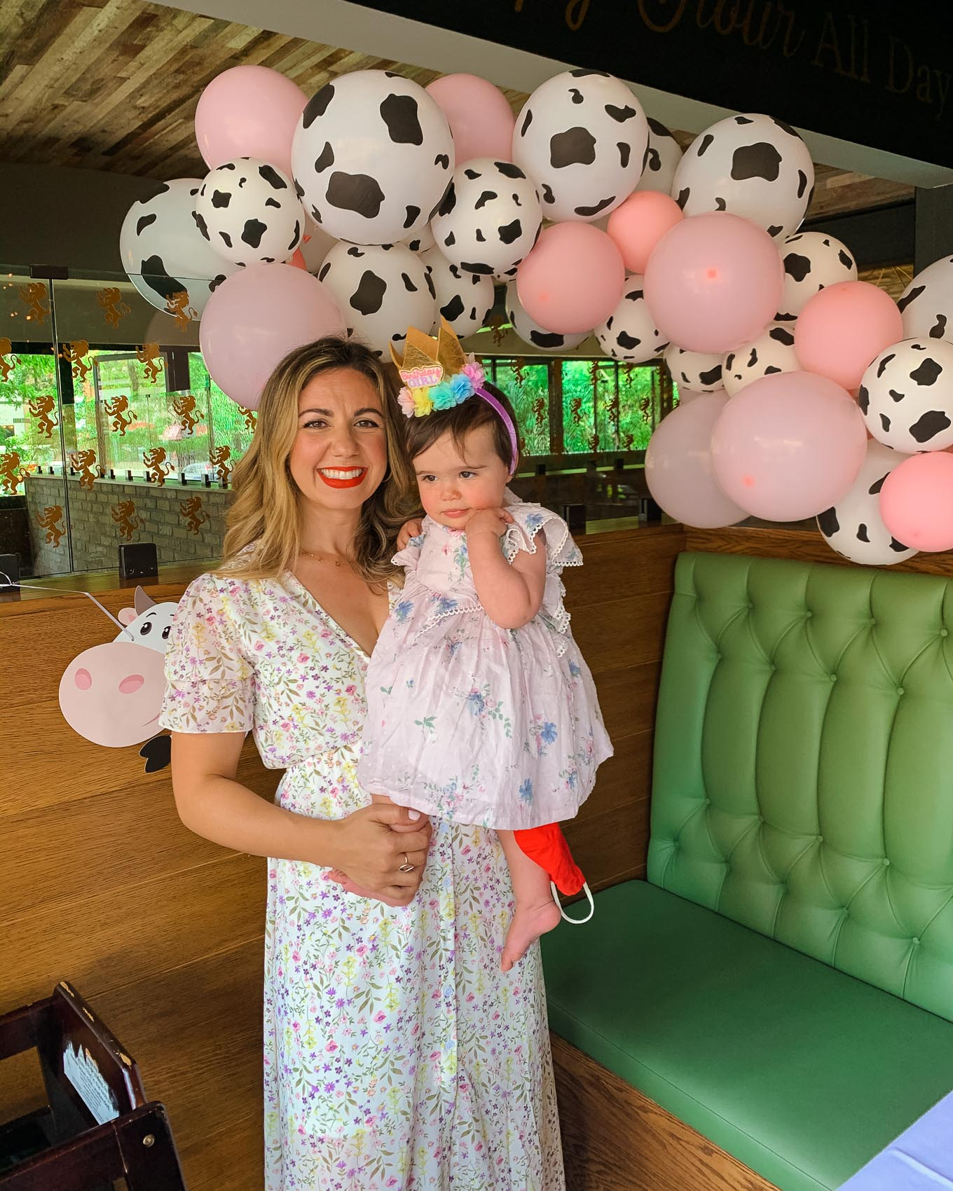 1st Birthday by popular Chicago lifestyle blog, Glass of Glam: image of a Mom holding her 1 year old baby daughter standing next to a Amazon QIYNAO White and Blacke Dairy Cow Happy Birthday Banner, Amazon Cow Print Beverage Napkins, Amazon Finypa Funny Cow Party Decorations Balloon 85pcs Arch Garland.