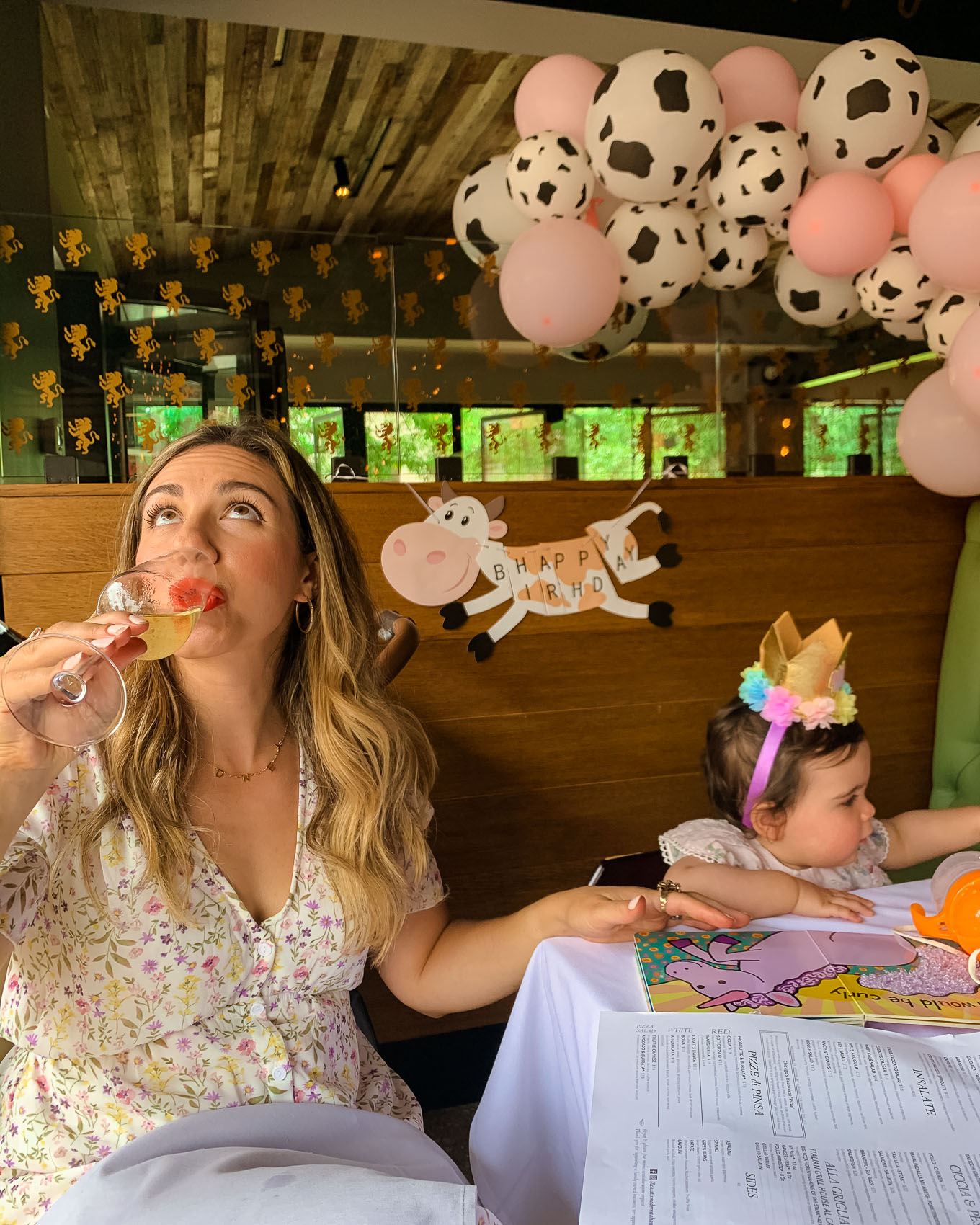 1st Birthday by popular Chicago lifestyle blog, Glass of Glam: image of a Mom and her 1 year old baby daughter sitting next to a Amazon QIYNAO White and Blacke Dairy Cow Happy Birthday Banner, Amazon Cow Print Beverage Napkins, Amazon Finypa Funny Cow Party Decorations Balloon 85pcs Arch Garland.