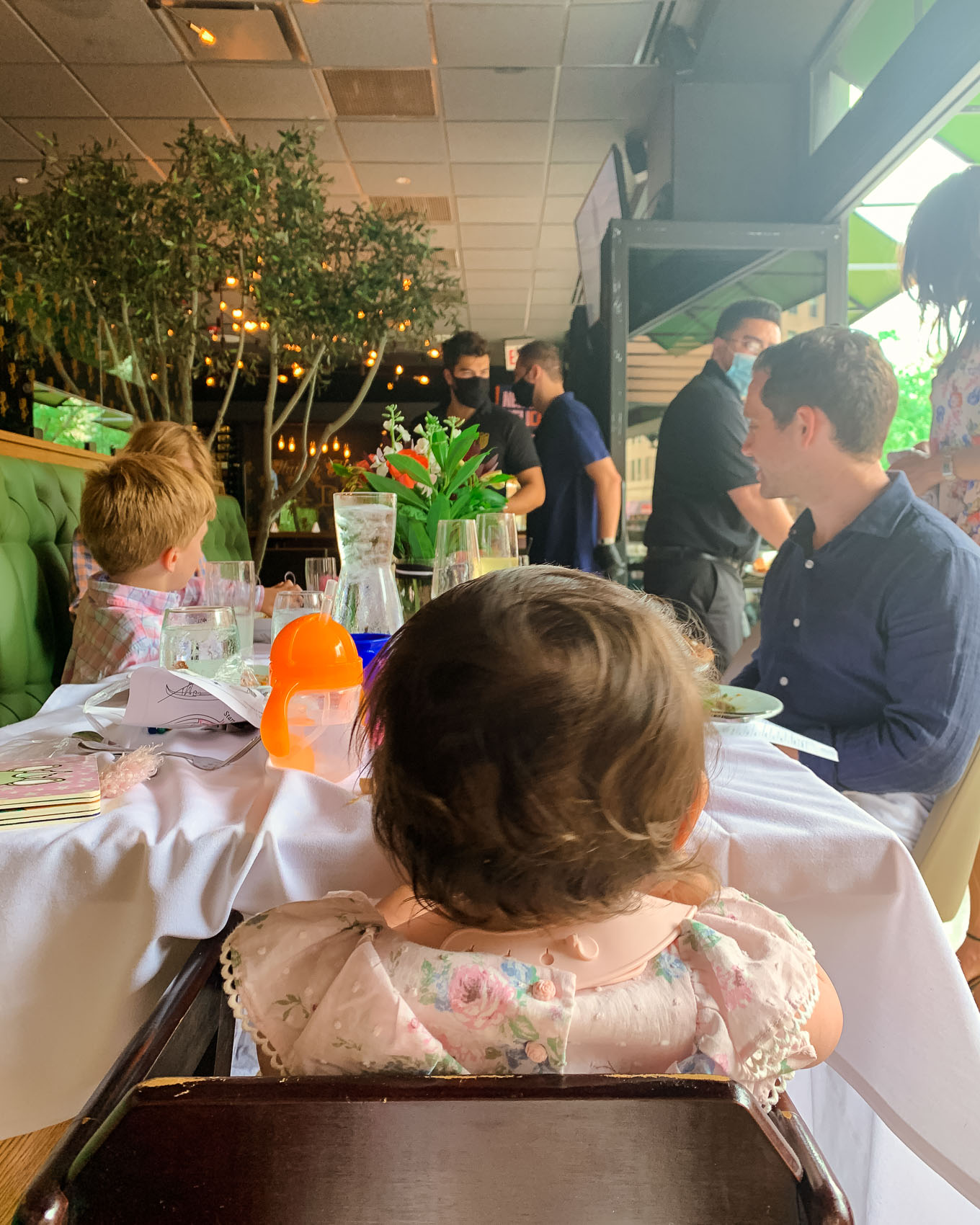 1st Birthday by popular Chicago lifestyle blog, Glass of Glam: image of a family sitting together at a restaurant table.