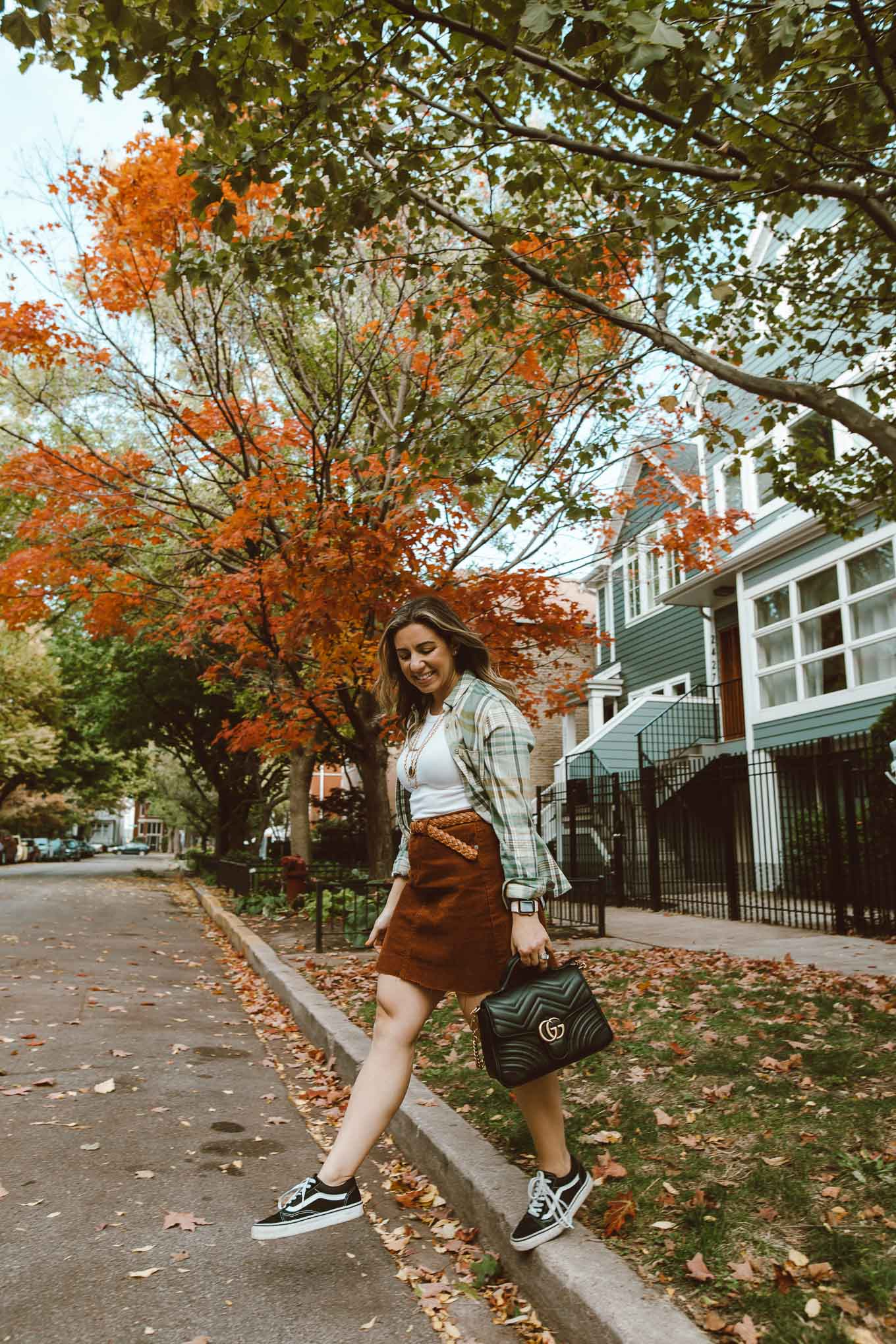 90's Fashion by popular Chicago fashion blog, Glass of Glam: image of a woman walking outside and wearing a corduroy skirt, Vans sneakers, flannel shirt, Target white tank top, Kendra Scott Davis Multistrand Necklace, and holding a Gucci bag.