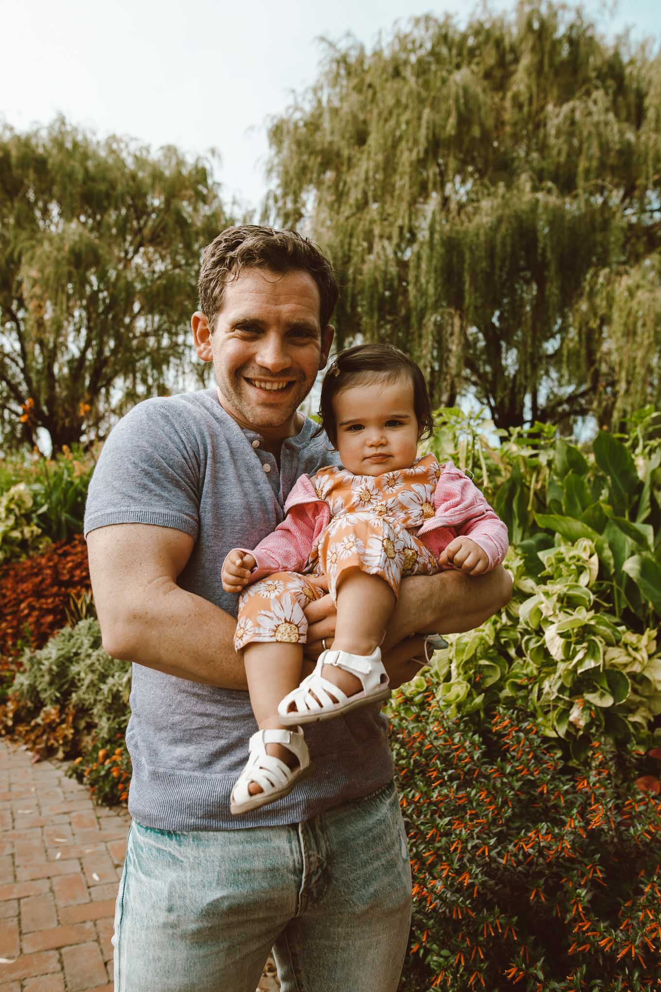 Botanic Garden by popular Chicago fashion blog, Glass of Glam: image of a dad holding his daughter at the Chicago Botanic Garden and wearing a henley t-shirt and Pat Pat Baby Girl Sunflowers Print Jumpsuits.
