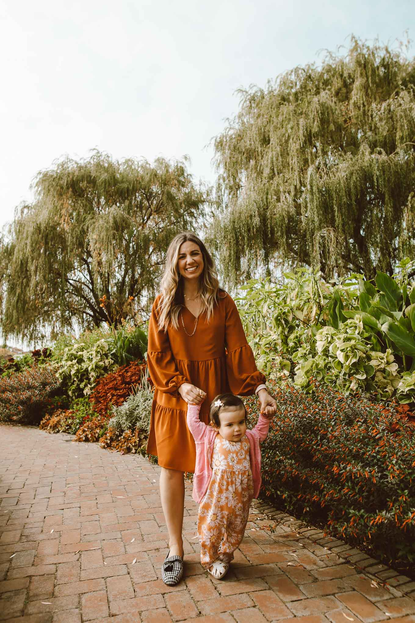 Botanic Garden by popular Chicago fashion blog, Glass of Glam: image of a woman walking through the Chicago Botanic Garden with her daughter and wearing a Amazon Amoretu Women Summer Tunic Dress V Neck Casual Loose Flowy Swing Shift Dresses, Kendra Scott Davis Vintage Gold Multi Strand Necklace In Golden Obsidian and Pat Pat Baby Girl Sunflowers Print Jumpsuits.