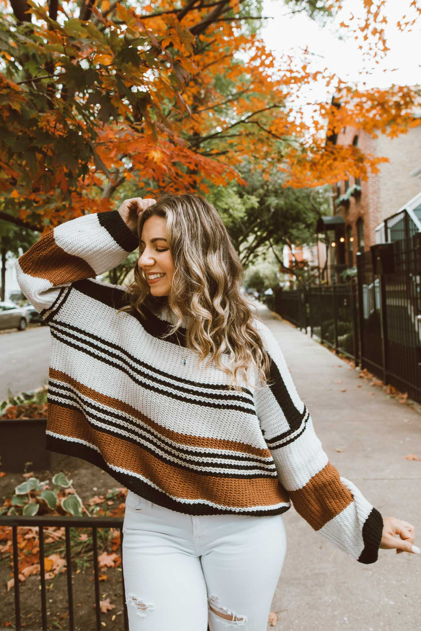 Fall Sweaters by popular Chicago fashion blog, Glass of Glam: image of a woman standing under a tree with orange leaves and wearing a Amazon ZESICA Women's Long Sleeve Crew Neck Striped Color Block Casual Loose Knitted Pullover Sweater, Old Navy Mid-Rise Distressed Rockstar Super Skinny White Ankle Jeans for Women, Gucci Gucci Jordaan GG canvas loafer, and Kendra Scott Elisa Gold Triple Strand Necklace In Abalone Shell.