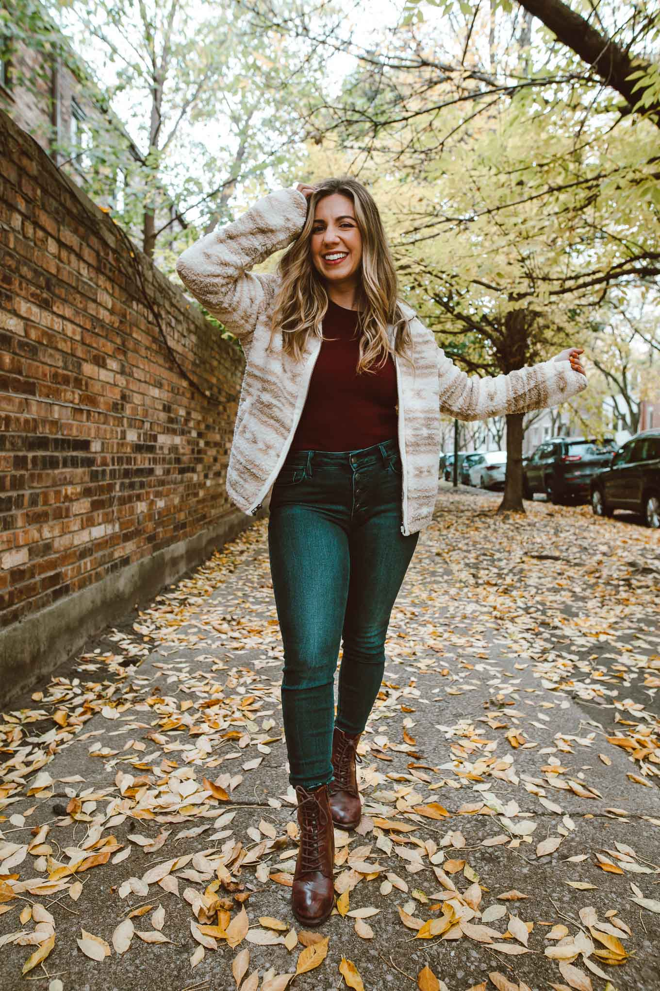 Sherpa Clothing by popular Chicago fashion blog, Glass of Glam: image of a woman walking through some leaves and wearing a red shirt, Old Navy Rockstar Jeans, Old Navy Cozy Sherpa Zip-Front Jacket for Women, and Patricia Nash Womens Sicily Leather Closed Toe Ankle Fashion Boots.