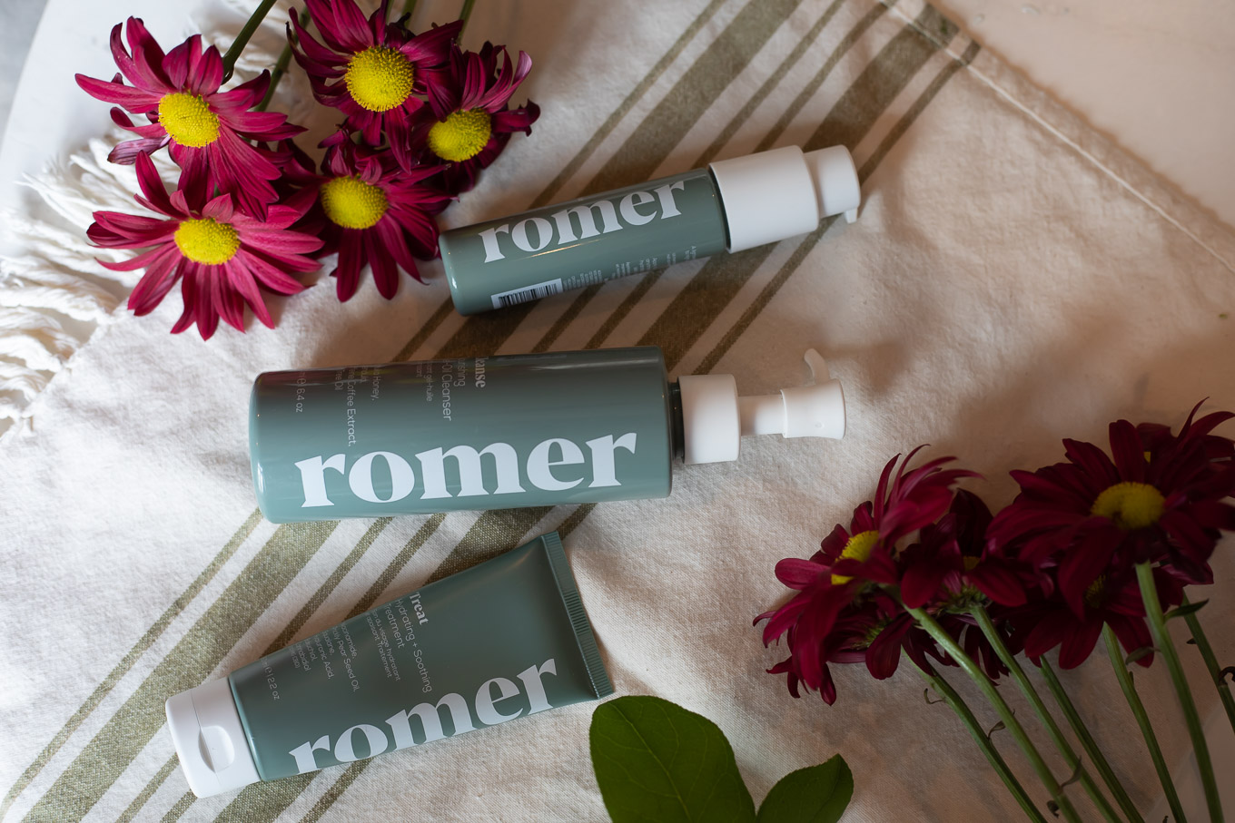 Romer Skincare by popular Chicago beauty blog, Glass of Glam: image of Romer Skincare products laying next to some purple daisies.