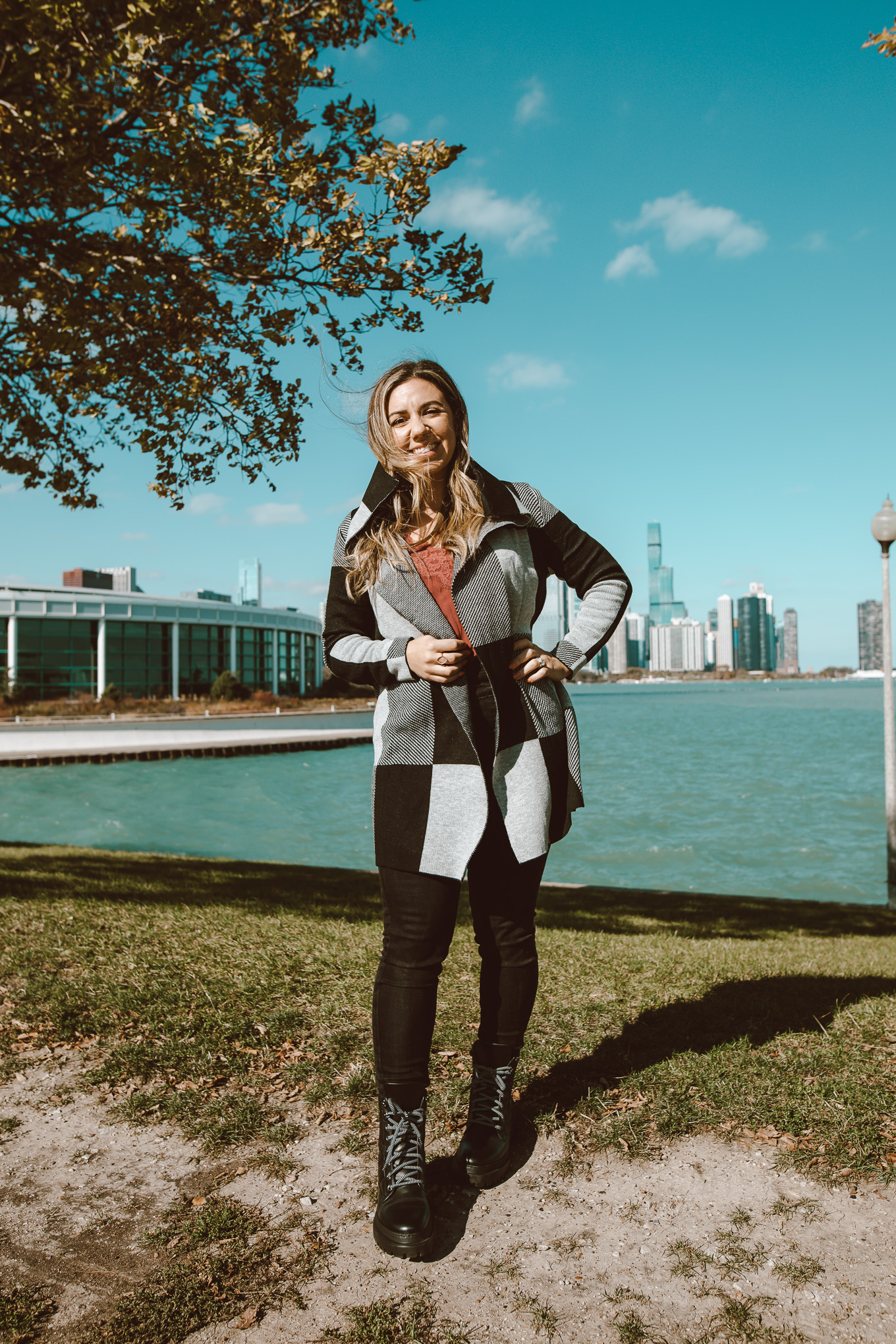 Cozy Sweater by popular Chicago fashion blog, Glass of Glam: image of a woman standing next to a lake with the Chicago skyline behind her and wearing a Amazon MEROKEETY Womens Plaid Long Sleeve Lapel Collar Drape Knit Cardigan, Abercrombie and Fitch lace cami, Ann Taylor Petite Sculpting Pocket High Rise Skinny Jeans In Jet Black Wash, and M. Gemi THE ETTA quilted combat boots.